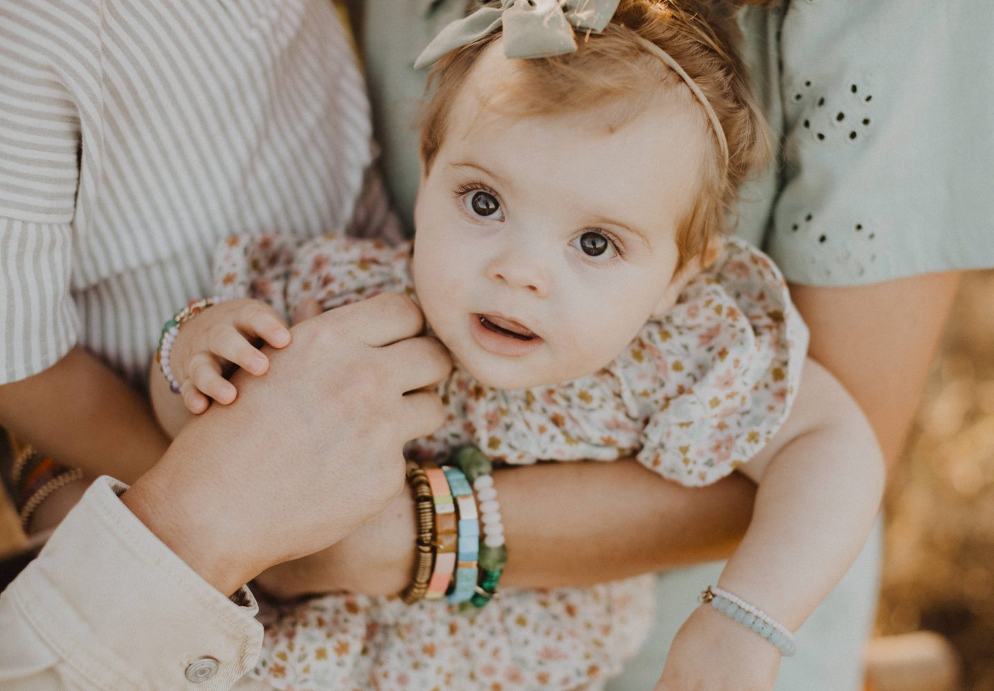 Life Update by popular lifestyle blog, Navy Grace: image of a baby girl wearing white mary jane shoes, a mint green bow head band, and a floral print dress and being held by her parents.