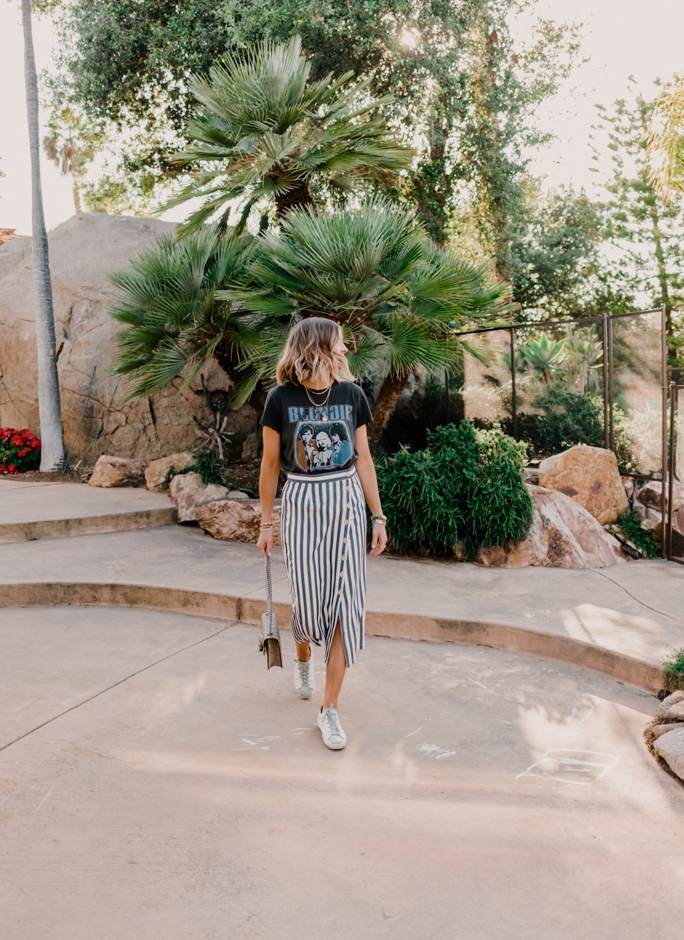 Midi Skirts by popular San Diego fashion blog, Navy Grace: image of woman standing outside by a palm tree and wearing a BB Dakota With A Twist Skirt, Glitter Blondie Tee  Junk Food brand: Junk Food, Nordstrom MiniShoulder Bag GUCCI, Golden Goose Sneakers, Anthropologie  Hover your mouse over an image to zoom.  Serena Stretch Bracelet and Anthropologie Verona Stretch Bracelet.