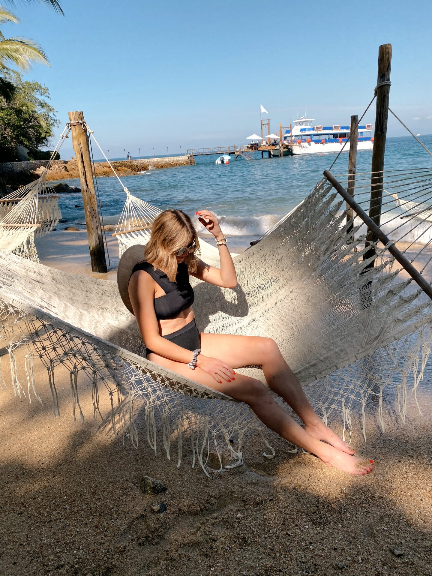 Summer Swimsuits by popular San Diego fashion blog, Navy Grace: image of a woman sitting in a macrame hammock and wearing a black bikini and straw hat.