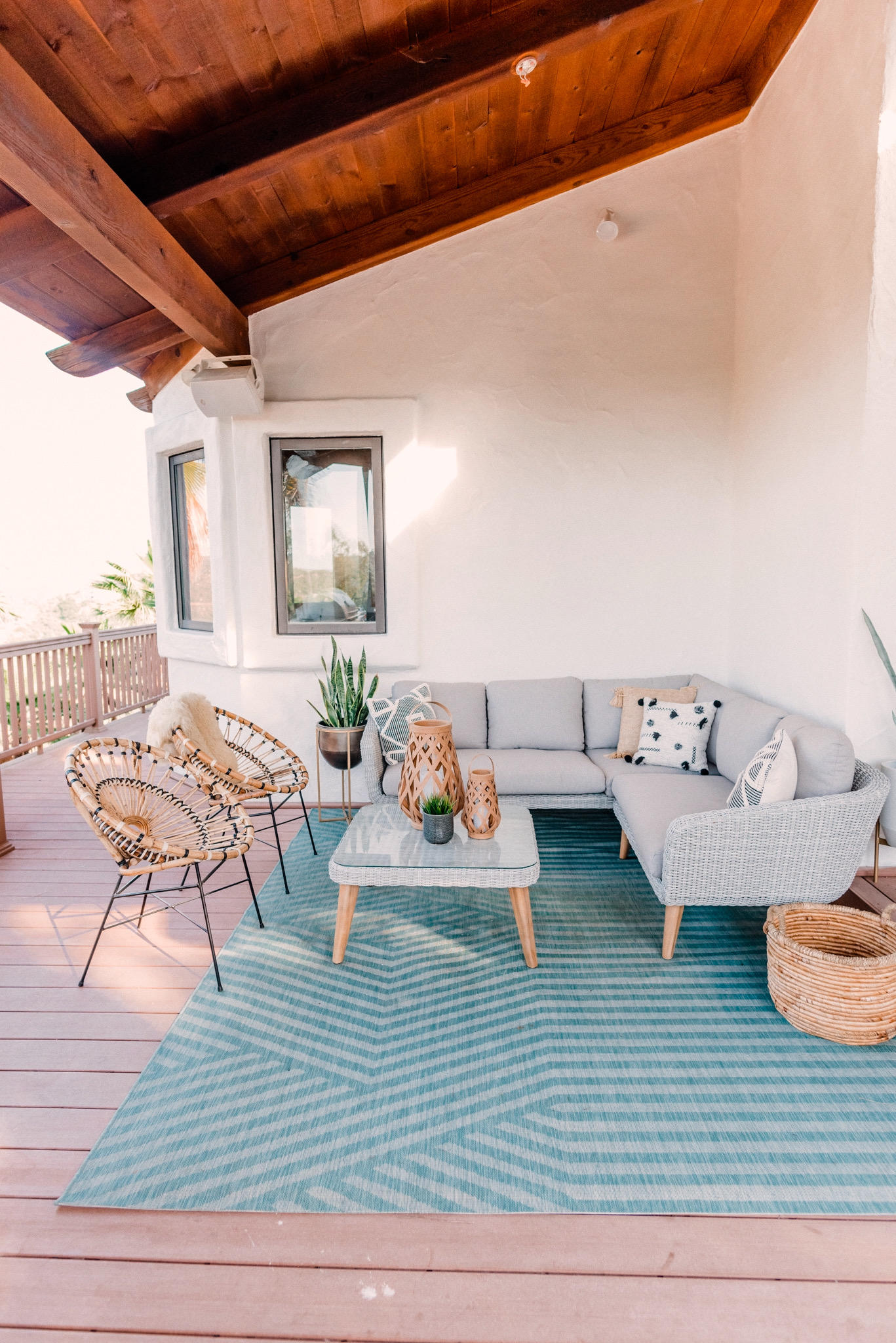 CB2 OUTDOOR DECOR featured by top San Diego lifestyle blogger, Navy Grace. | CB2 Furniture by popular San Diego life and style blog, Navy Grace: image of a CB2 hurricane lantern, Seminyak Gray Planter, snake tongue plants, blue outdoor rug, woven wicker outdoor couch, woven wicker coffee table, woven basket, and Rattan chairs.