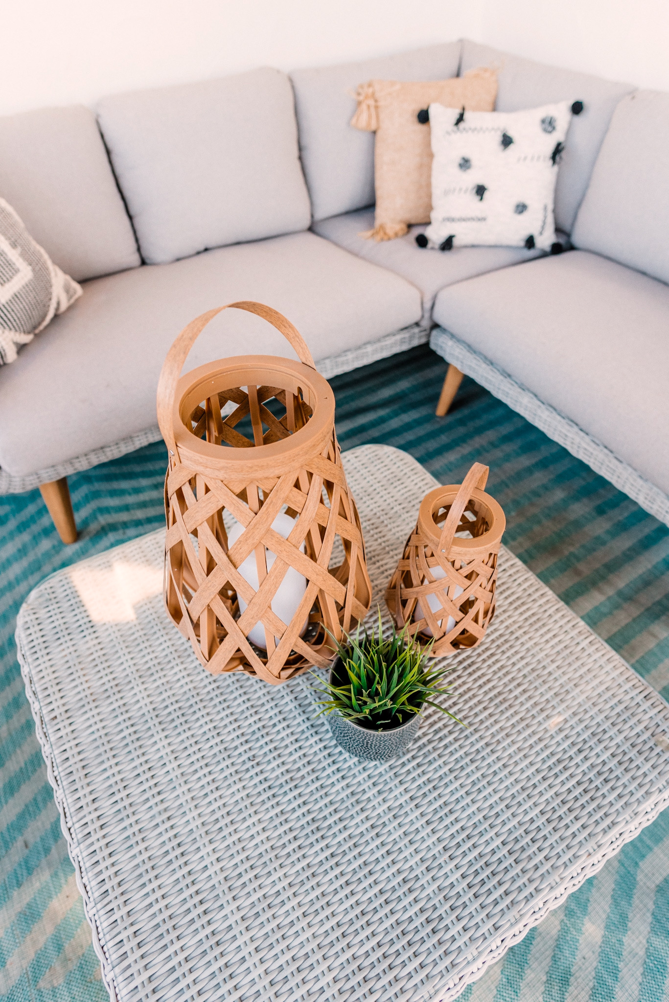 CB2 OUTDOOR DECOR featured by top San Diego lifestyle blogger, Navy Grace.   CB2 Furniture by popular San Diego life and style blog, Navy Grace: image of a CB2 hurricane lantern, Seminyak Gray Planter, snake tongue plants, blue outdoor rug, woven wicker outdoor couch, woven wicker coffee table, woven basket, and Rattan chairs.