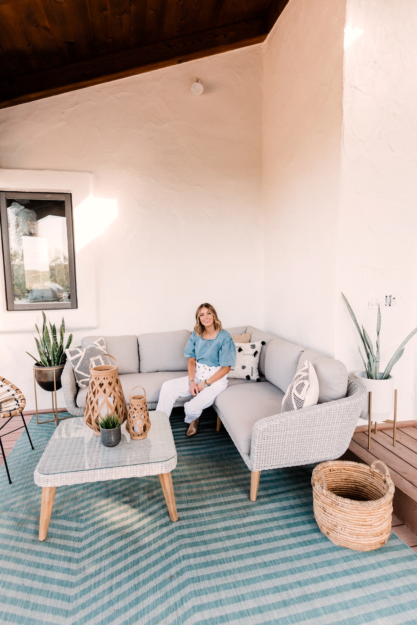 CB2 OUTDOOR DECOR featured by top San Diego lifestyle blogger, Navy Grace.   CB2 Furniture by popular San Diego life and style blog, Navy Grace: image of a woman outside on her patio decorated with CB2 hurricane lantern, Seminyak Gray Planter, snake tongue plants, blue outdoor rug, woven wicker outdoor couch, woven wicker coffee table, woven basket, and Rattan chairs.