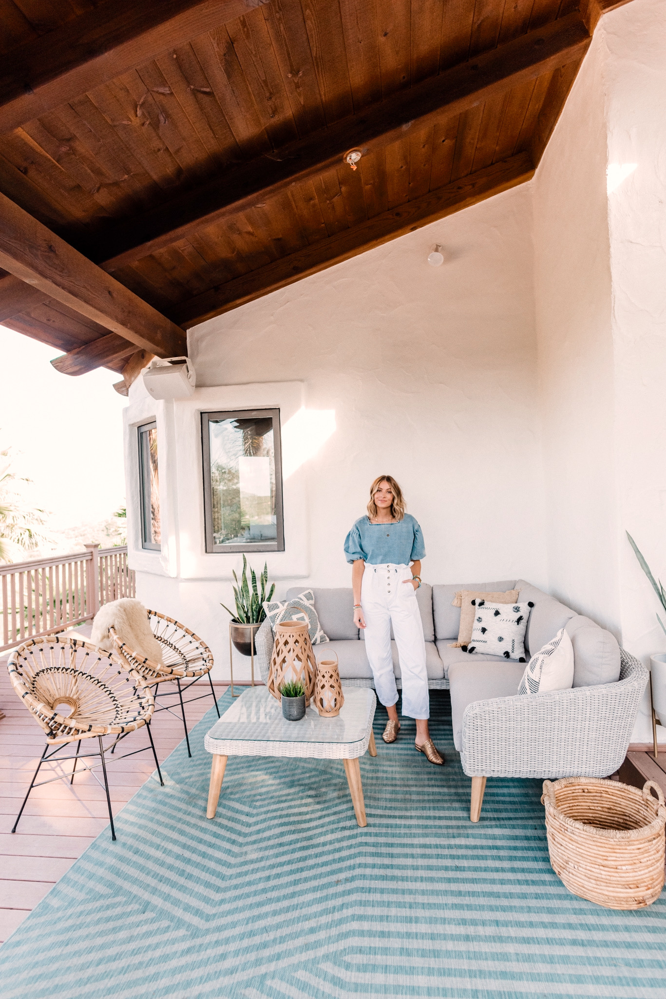 CB2 OUTDOOR DECOR featured by top San Diego lifestyle blogger, Navy Grace.   CB2 Furniture by popular San Diego life and style blog, Navy Grace: image of a woman standing outside on her patio decorated with a CB2 hurricane lantern, Seminyak Gray Planter, snake tongue plants, blue outdoor rug, woven wicker outdoor couch, woven wicker coffee table, woven basket, and Rattan chairs.