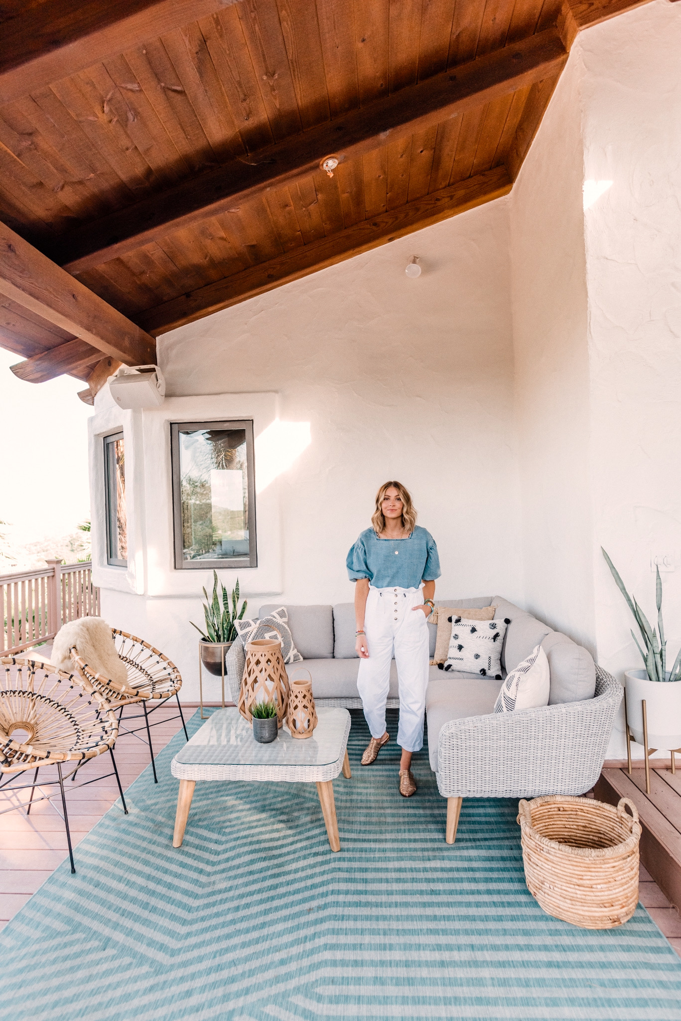 CB2 OUTDOOR DECOR featured by top San Diego lifestyle blogger, Navy Grace.   CB2 Furniture by popular San Diego life and style blog, Navy Grace: image of a woman outside on her patio decorated with a CB2 hurricane lantern, Seminyak Gray Planter, snake tongue plants, blue outdoor rug, woven wicker outdoor couch, woven wicker coffee table, woven basket, and Rattan chairs.