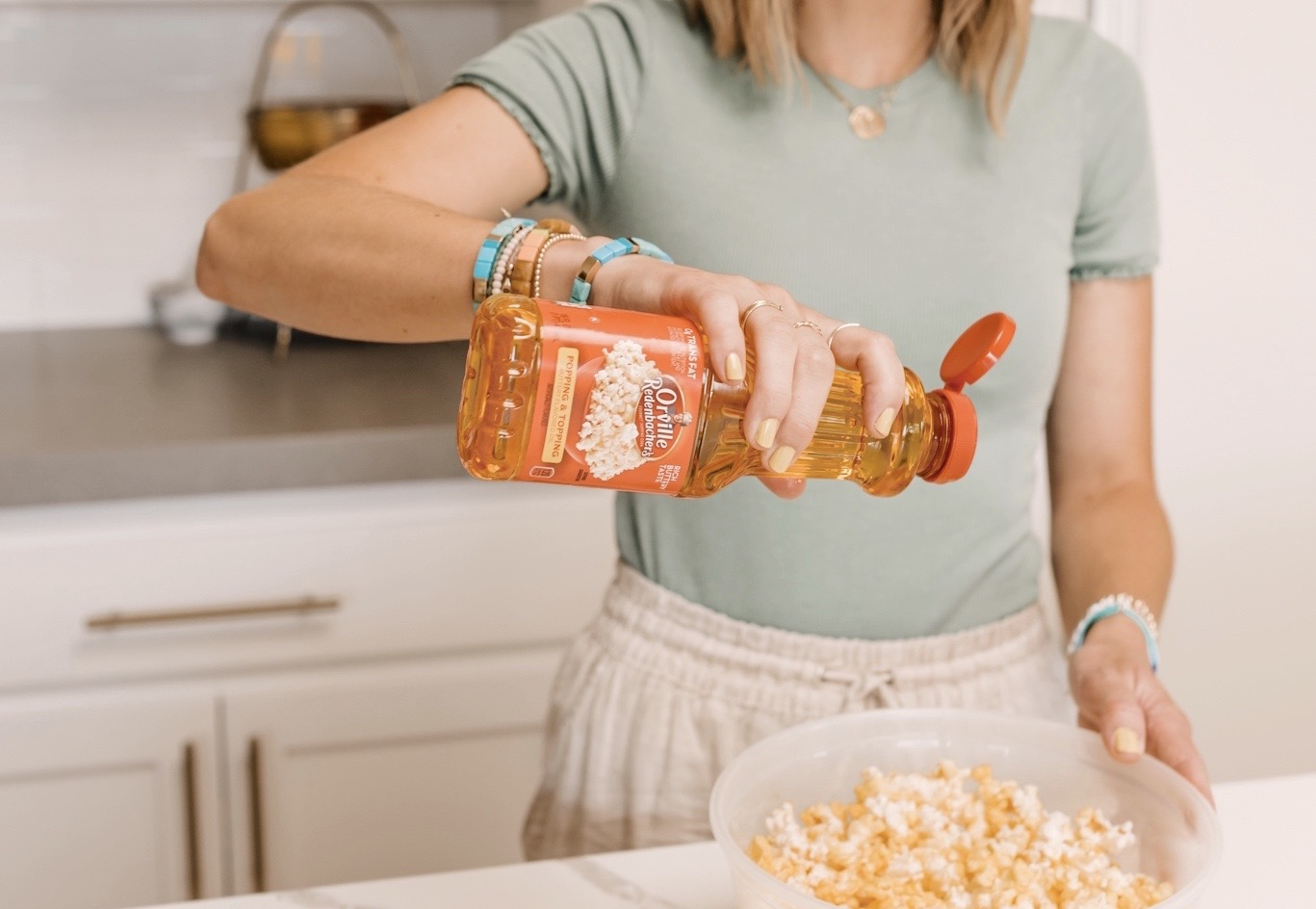 Orville Redenbacher's Popcorn by popular San Diego lifestyle blog, Navy Grace: image of a woman putting Orville Redenbacher's popping and topping on a bowl of popcorn.