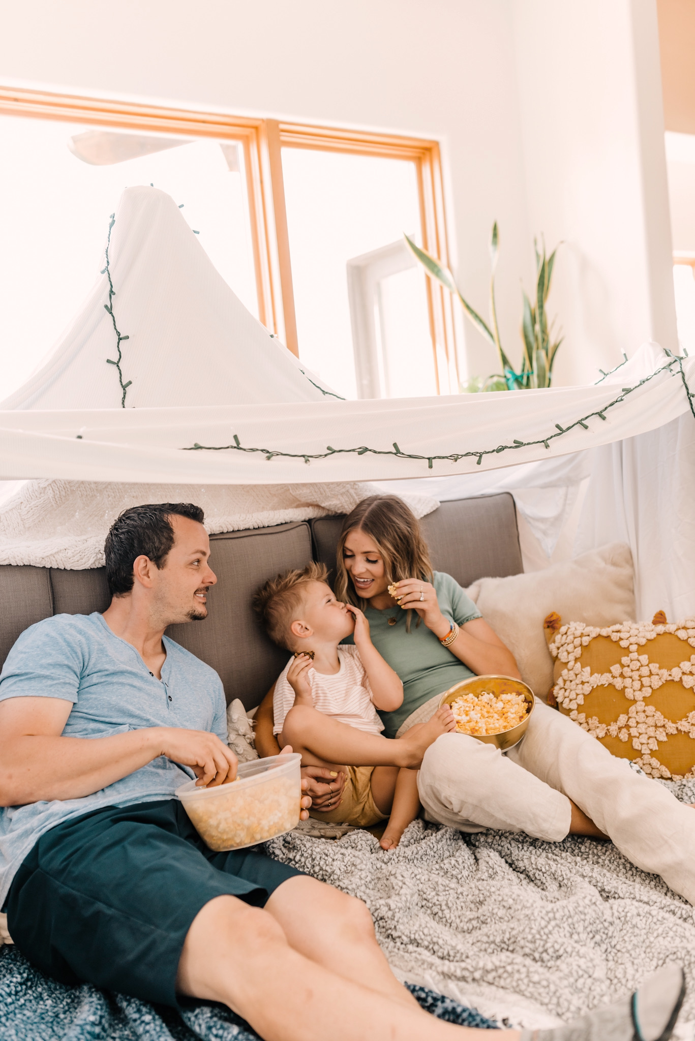 Orville Redenbacher's Popcorn by popular San Diego lifestyle blog, Navy Grace: image of a mom, dad, and young boy sitting in a blanket fort and eating Orville Redenbacher's popcorn.