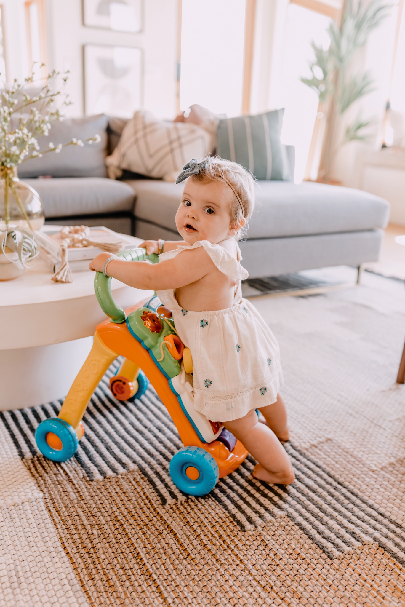 AMAZON FAVORITES: 20 GIFT IDEAS FOR ONE YEAR OLDS featured by top San Diego lifestyle blogger, Navy Grace | Gift Ideas for One Year Old by popular San Diego motherhood blog, Navy Grace: image of a one year old girl playing with a Sit to Stand Learning Walker.