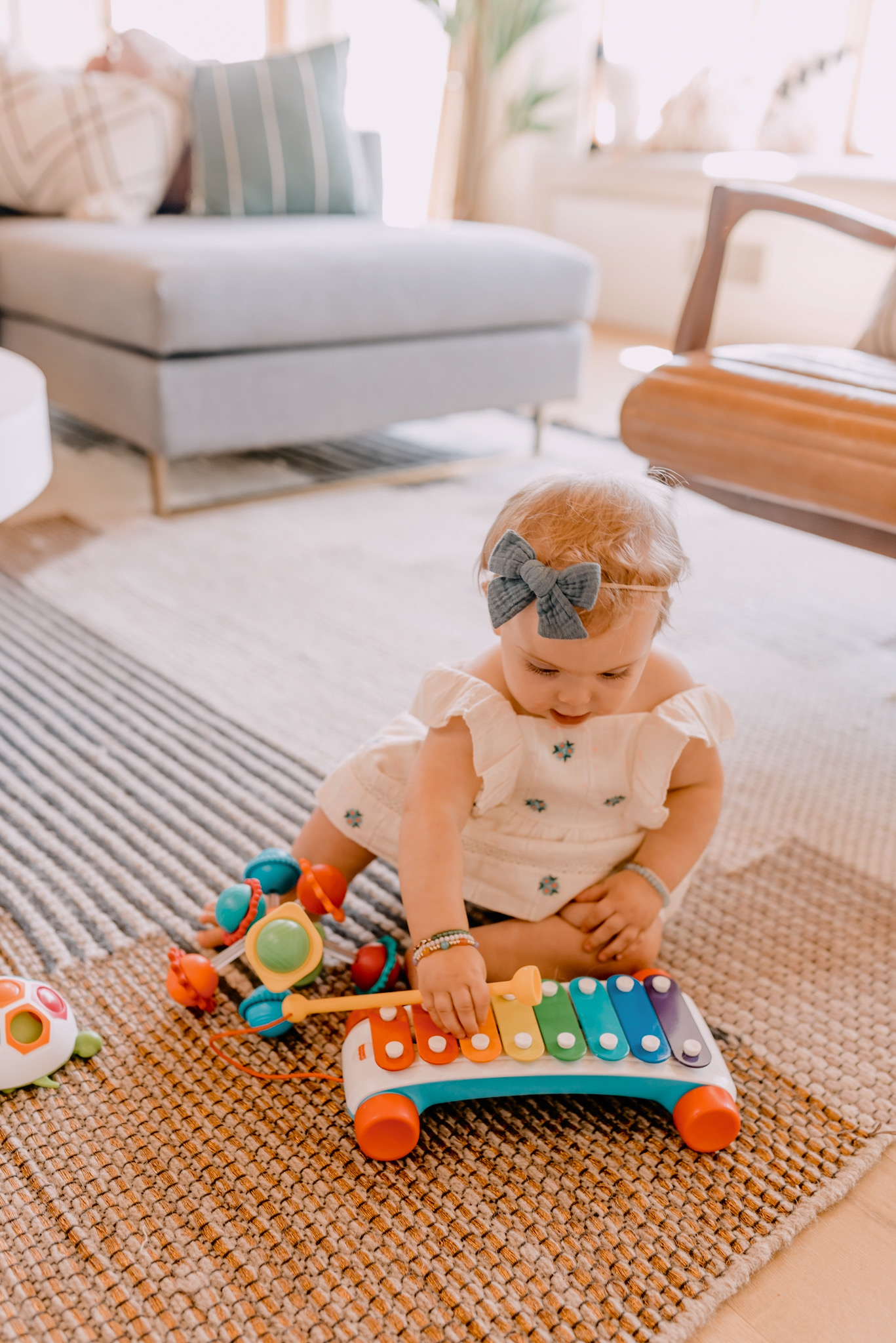 AMAZON FAVORITES: 20 GIFT IDEAS FOR ONE YEAR OLDS featured by top San Diego lifestyle blogger, Navy Grace | Gift Ideas for One Year Old by popular San Diego motherhood blog, Navy Grace: image of a one year old girl playing with a toy xylophone.