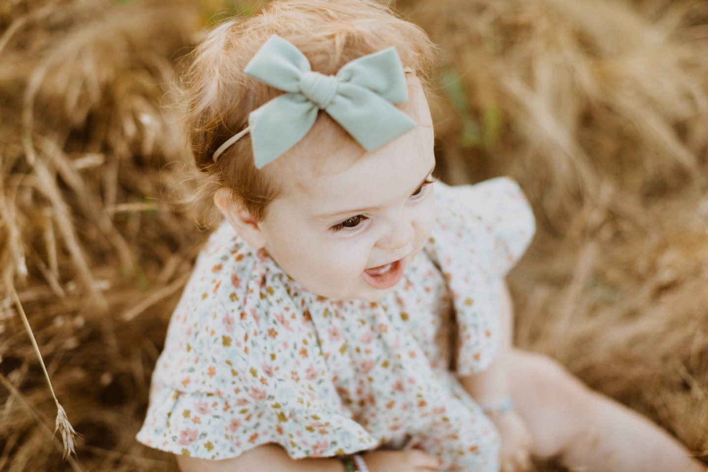 Family Photo Ideas by popular San Diego lifestyle blog, Navy Grace: image of a little girl sitting in a field and wearing a Rylee and Cru floral print dress.