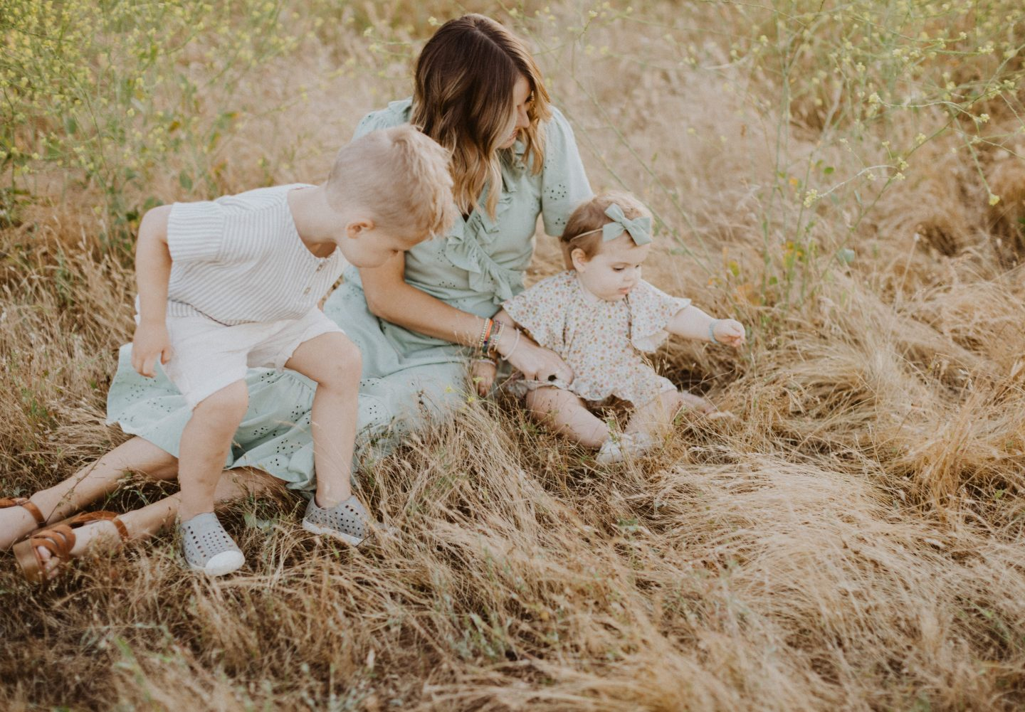 Family Photo Ideas by popular San Diego lifestyle blog, Navy Grace: image of a and her two children sitting together in a field and wearing Rylee and Cru clothing, Zappos Native Kids Shoes Jefferson, ASOS DESIGN ruffle broderie midi dress in sage green, and Sezane High Thomas Sandals.