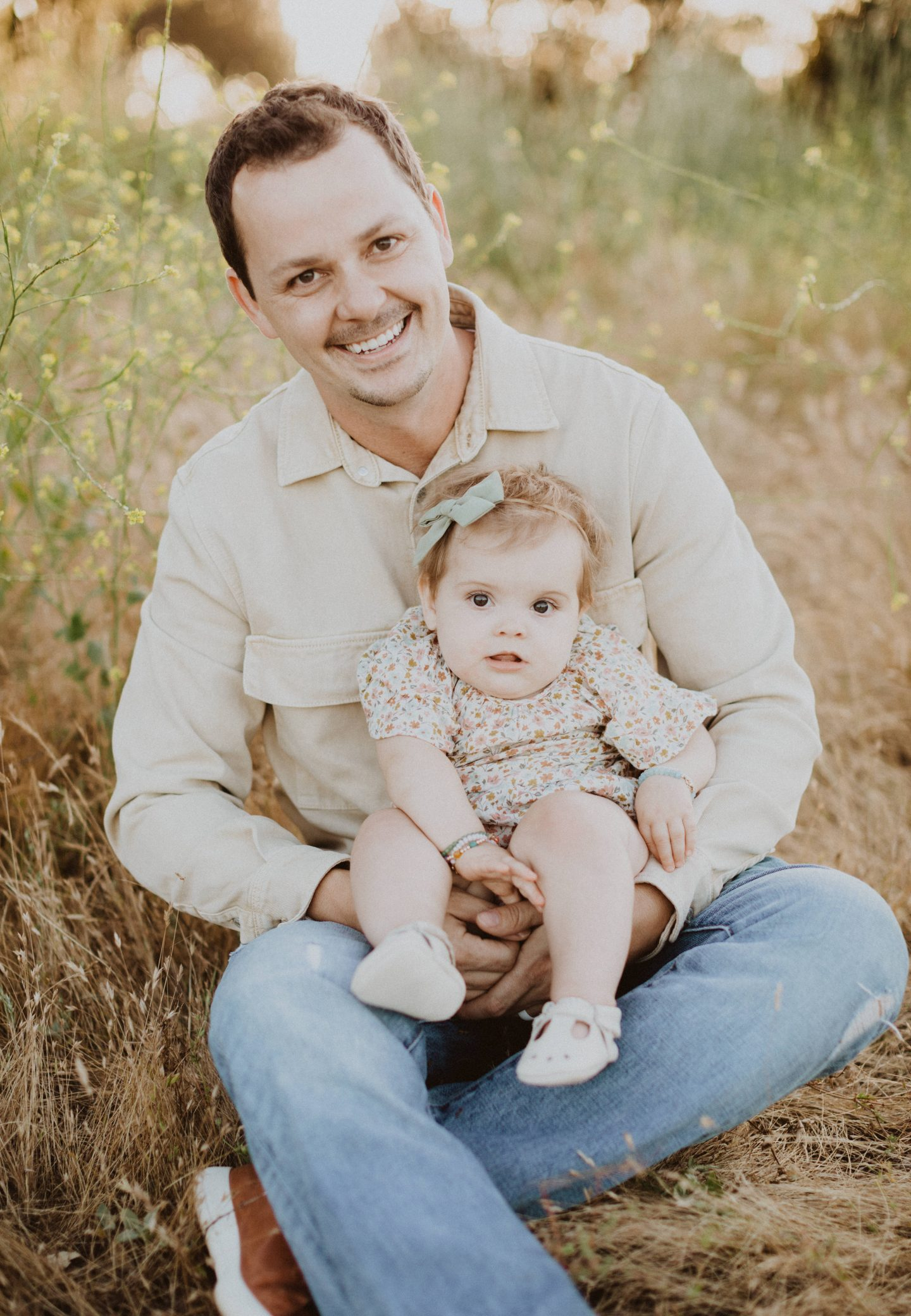Family Photo Ideas by popular San Diego lifestyle blog, Navy Grace: image of a dad sitting in a field while holding his baby daughter and wearing a Rylee and Cru floral print dress, Nordstrom COLE HAAN GrandPro Low Top Sneaker, and Nordstrom FRANK AND OAK Marled Chambray Button-Up Shirt.