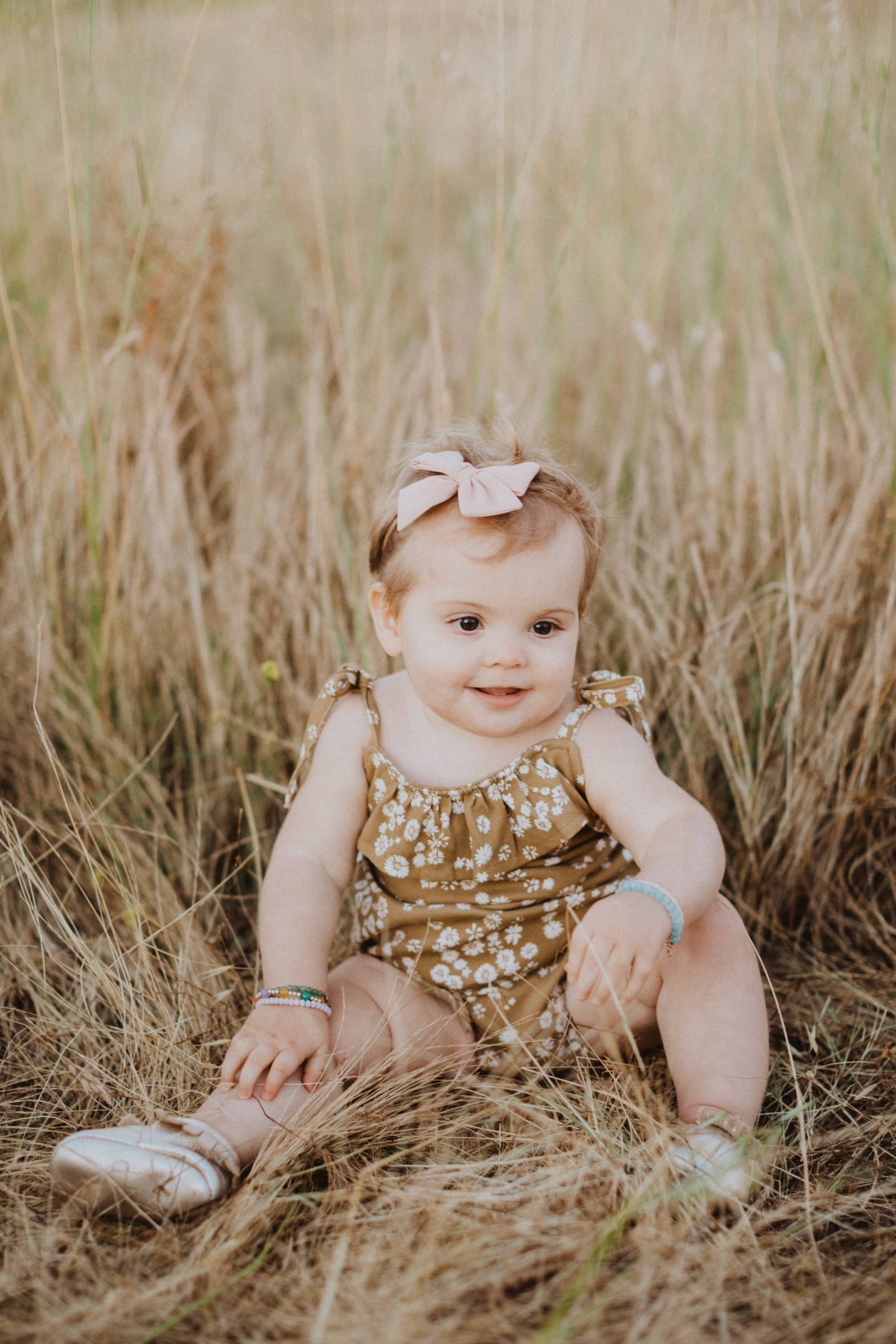 Life Update by popular lifestyle blog, Navy Grace: image of a baby sitting in some tall grass and wearing gold Freshly Picked Moccasins, a pink bow head band, and a daisy romper.