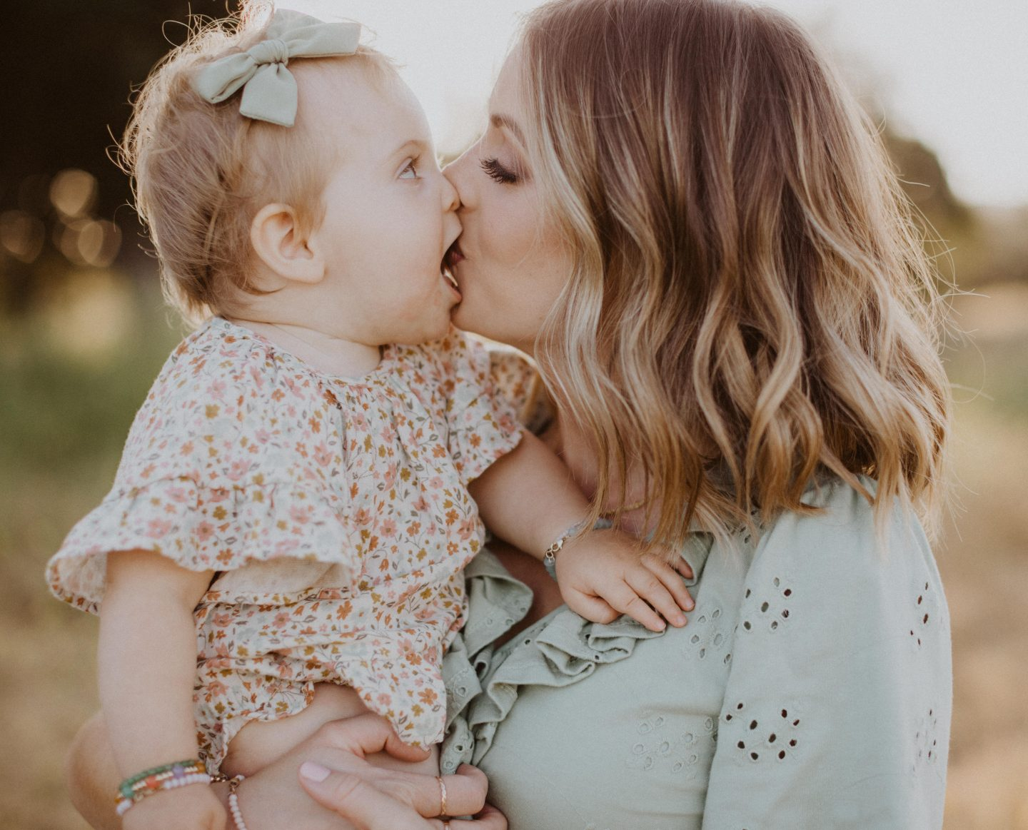 Family Photo Ideas by popular San Diego lifestyle blog, Navy Grace: image of a mother holding her young daughter in a field as the kiss on the lips and are wearing Rylee and Cru floral print dress, ASOS DESIGN ruffle broderie midi dress in sage green, and Sezane High Thomas Sandals.