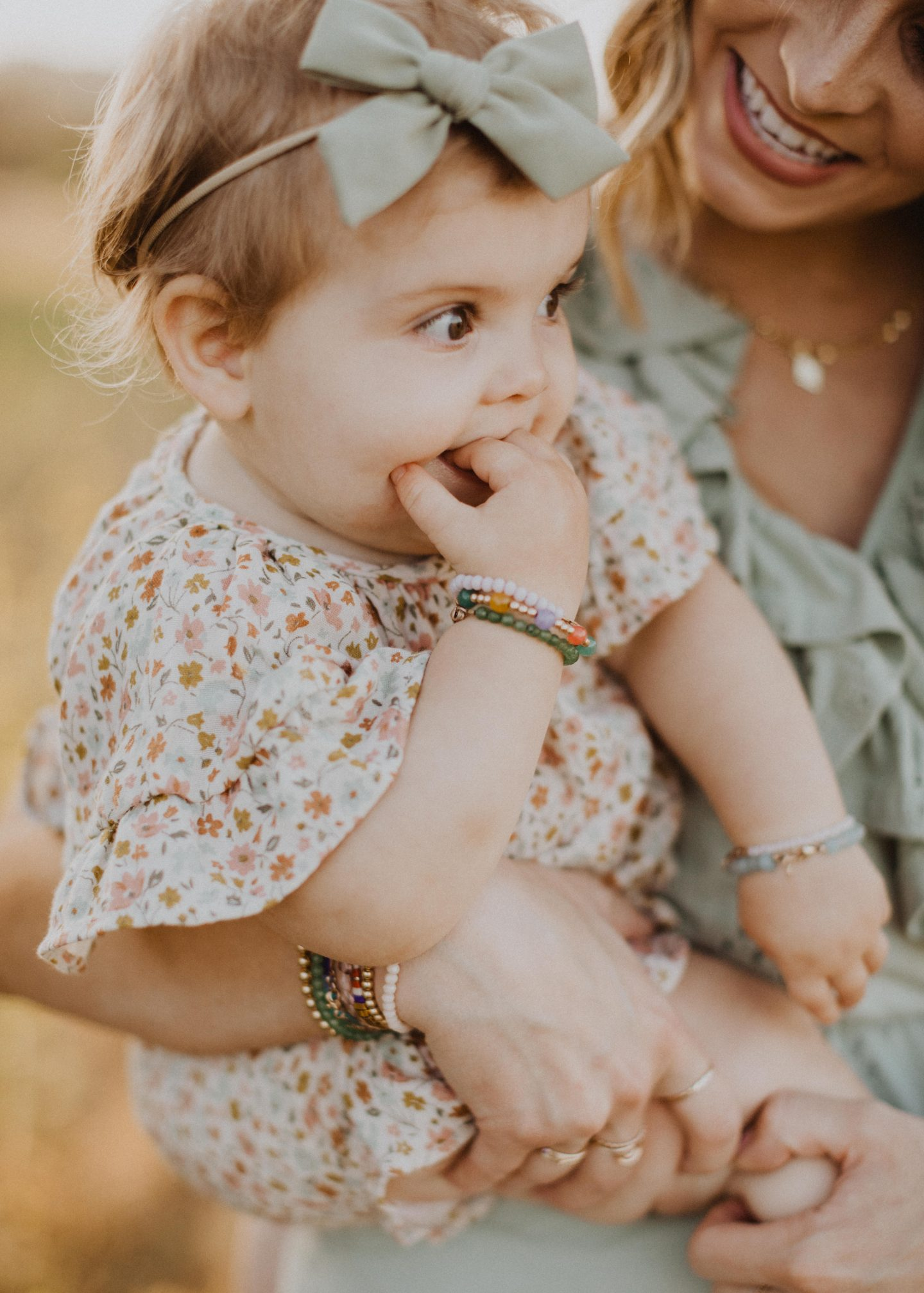 Family Photo Ideas by popular San Diego lifestyle blog, Navy Grace: image of a little girl held by her mom in a field and wearing a Rylee and Cru floral print dress.