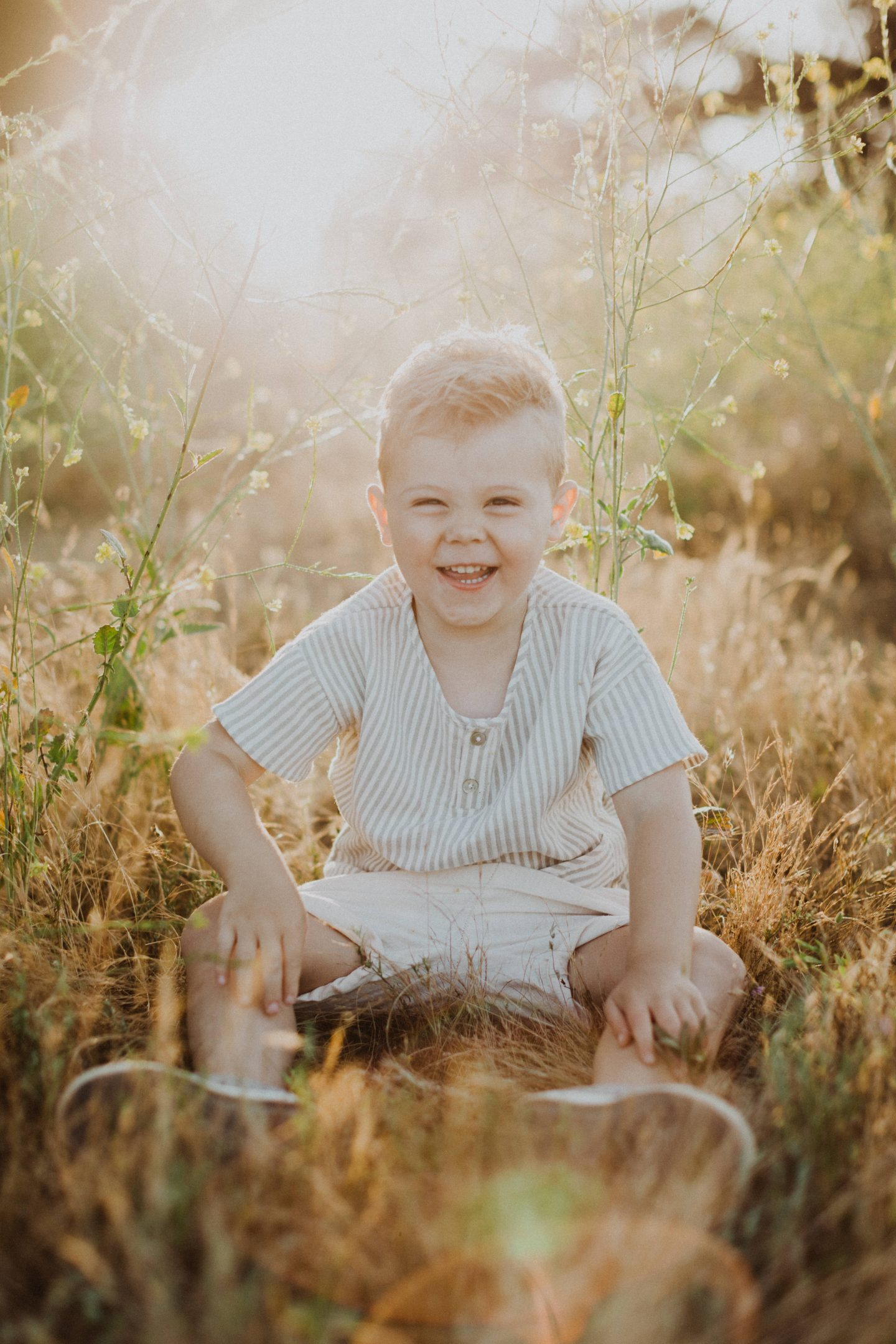 Family Photo Ideas by popular San Diego lifestyle blog, Navy Grace: image of a little boy sitting in a field and wearing Rylee and Cru clothing and Zappos Native Kids Shoes Jefferson.