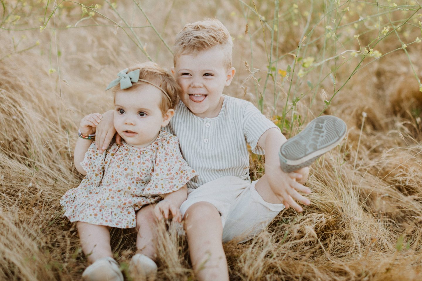 Family Photo Ideas by popular San Diego lifestyle blog, Navy Grace: image of a little boy and girl sitting together in a field and wearing Rylee and Cru clothing and Zappos Native Kids Shoes Jefferson.