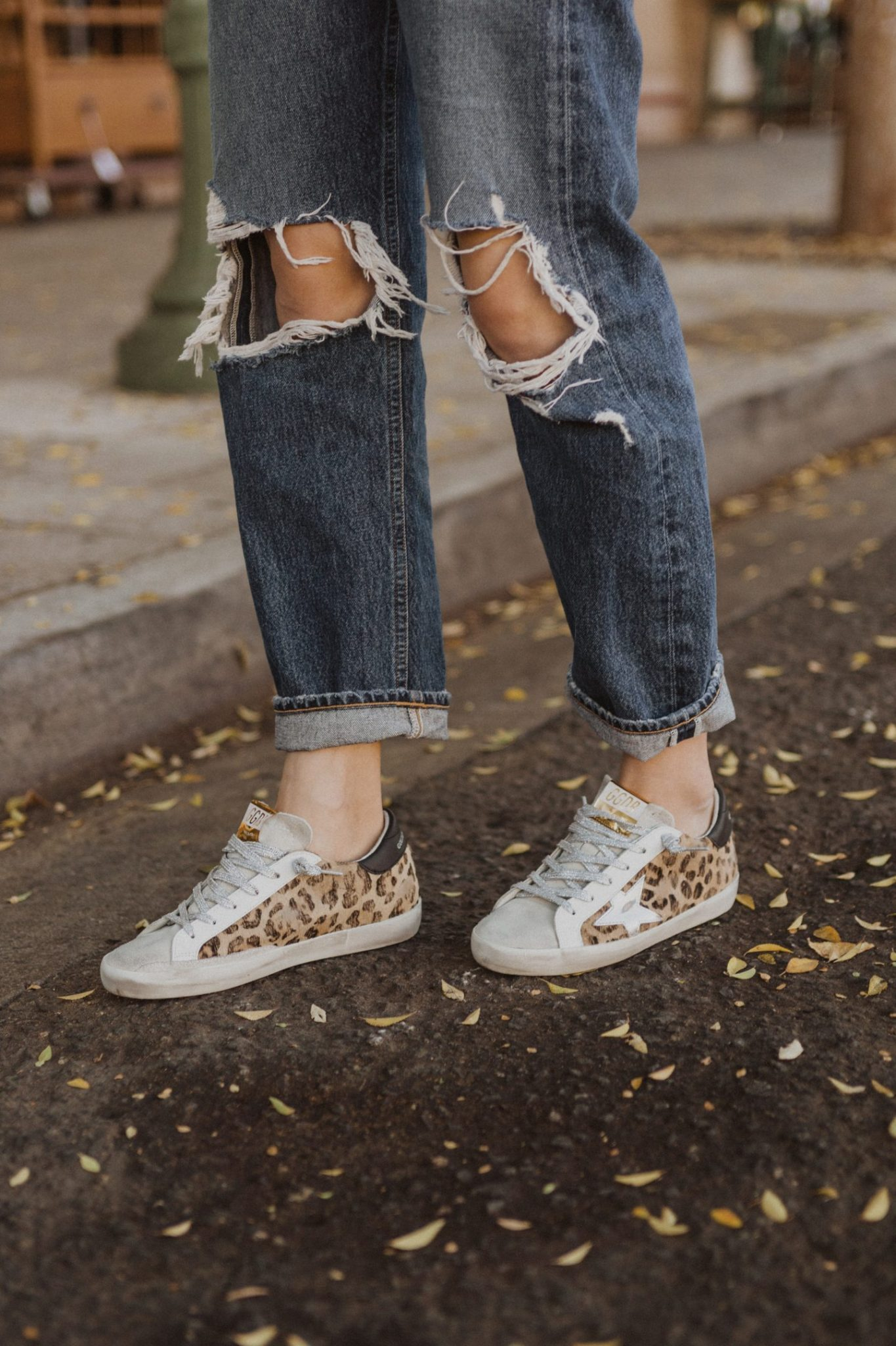 Golden Goose Sneakers by popular San Diego fashion blog, Navy Grace: image of a woman wearing a pair of Golden Goose distressed Superstar sneakers. Golden Goose Sneakers by popular San Diego fashion blog, Navy Grace: image of a woman wearing a pair of Golden Goose leopard print sneakers and 90s Mid Rise Loose Fit  AGOLDE brand jeans.