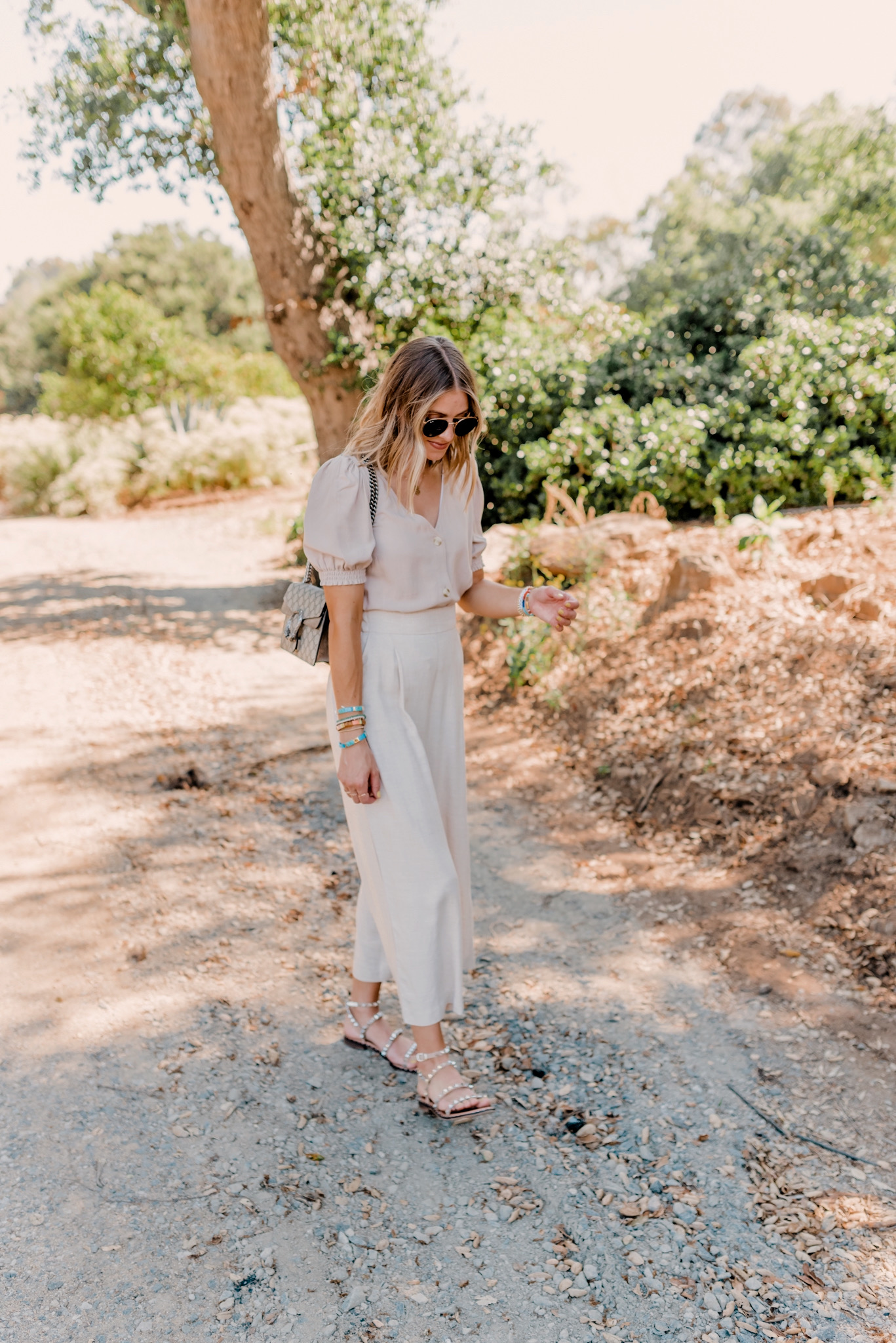 Neutral Colors Clothes by popular San Diego fashion blog, Navy Grace: image of a woman walking outside and wearing a H&M Puff-sleeved Blouse, H&M Wide-cut Pants, Steve Madden TRAVEL TAN sandals, Ray-Ban sunglasses and holding a Gucci Dionysus GG Supreme mini bag.
