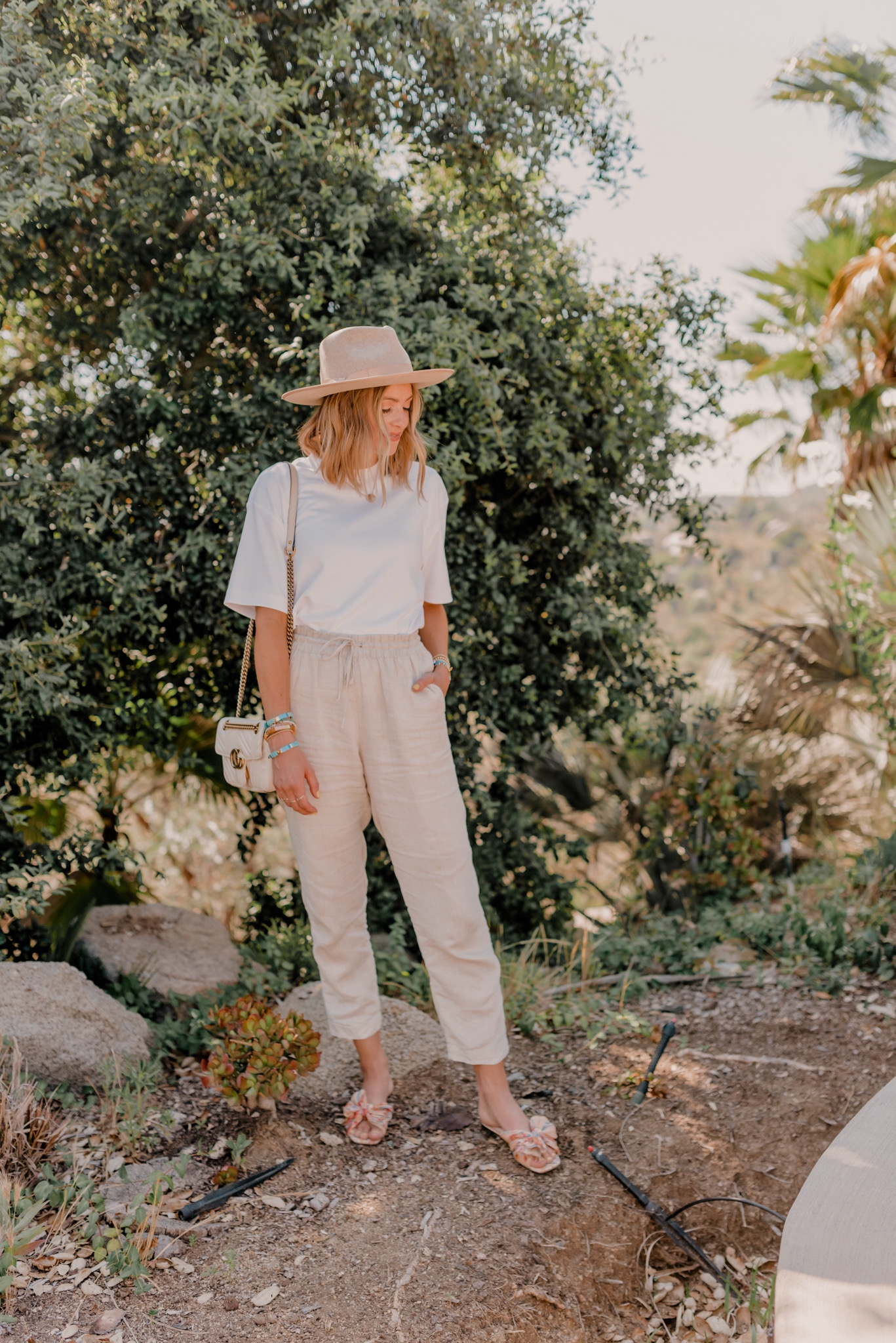 Linen Blend by popular San Diego fashion blog, Navy Grace: image of a woman standing outside and wearing H&M Linen Joggers, Target Prologue Short Sleeve T-Shirt, Loeffler Randall Daphne Flat Floral Sandals, Gigi Pip Monroe Oatmeal rancher hat, and holding a Nordstrom Small Matelassé Leather Shoulder Bag GUCCI.