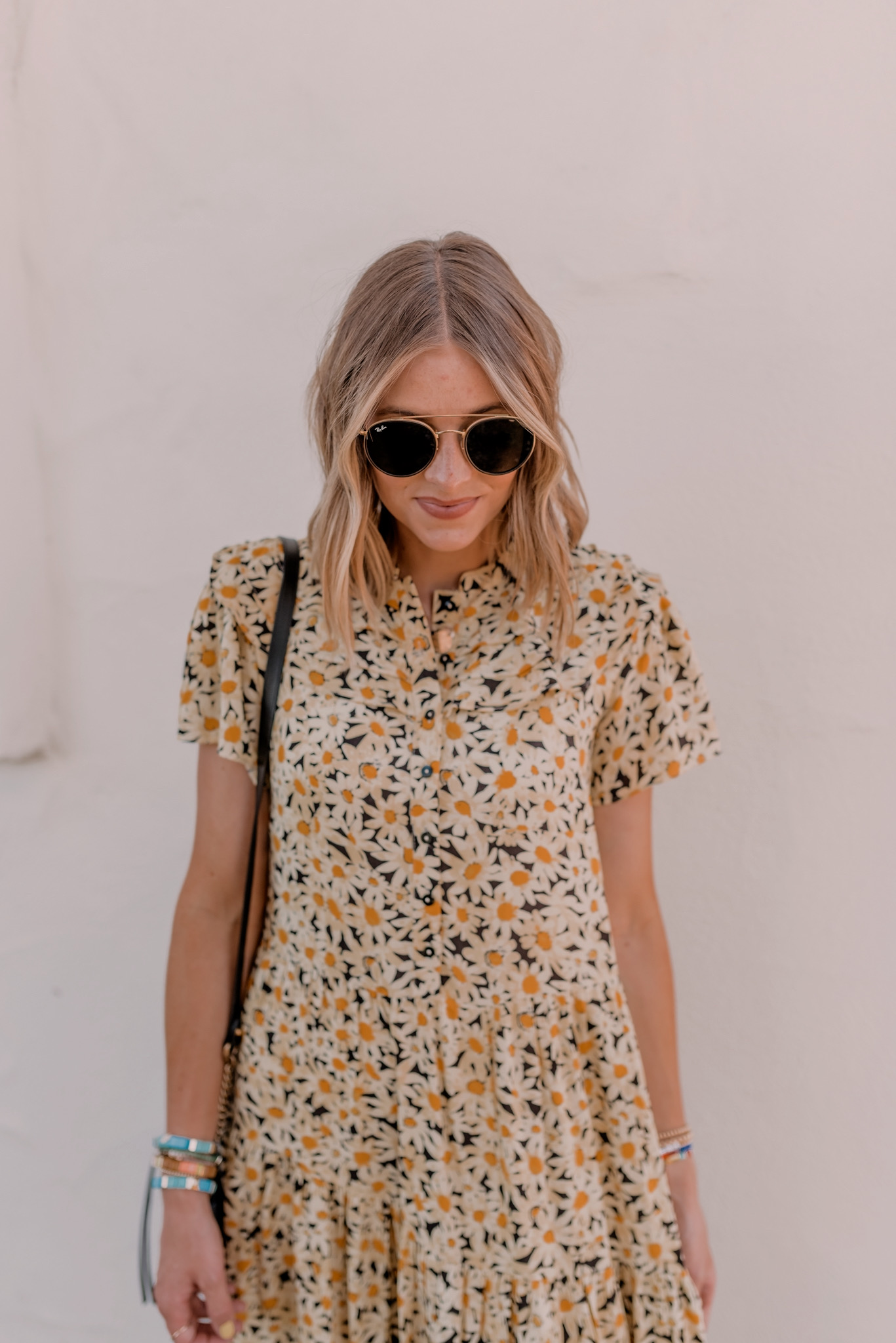 Summer Dresses by popular San Diego fashion blog, Navy Grace: image of a woman standing outside by a white stucco wall and wearing a TopShop Yellow Daisy Grandad Midi Shirt Dress, H&M gold metallic sandals, Ray-Ban sunglasses, and holding a Gucci GG Marmont Matelassé Mini Bag.