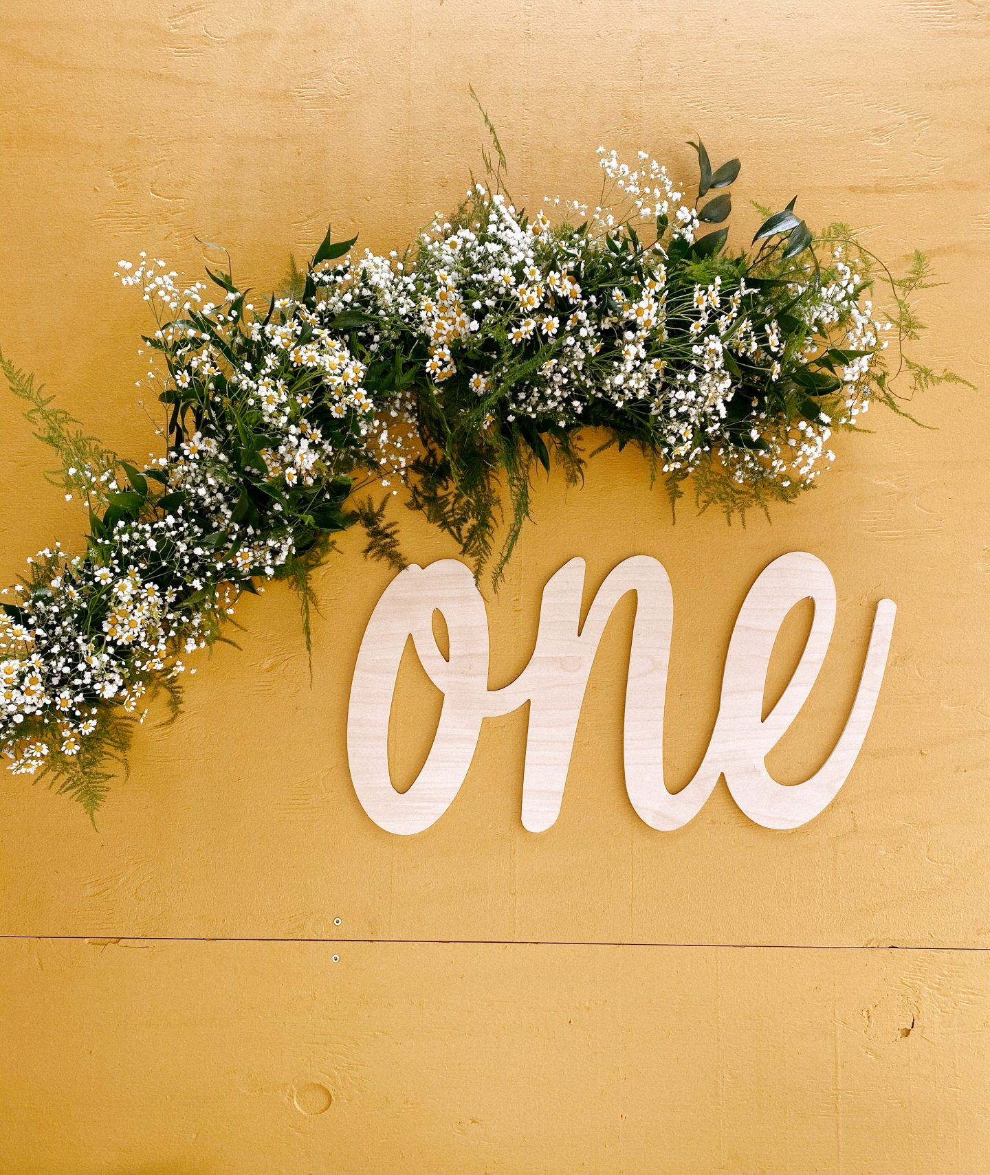 Daisy Theme Party by popular San Diego lifestyle blog, Navy Grace: image of a mustard yellow backdrop, wooden 'one' sign, and daisy garland.