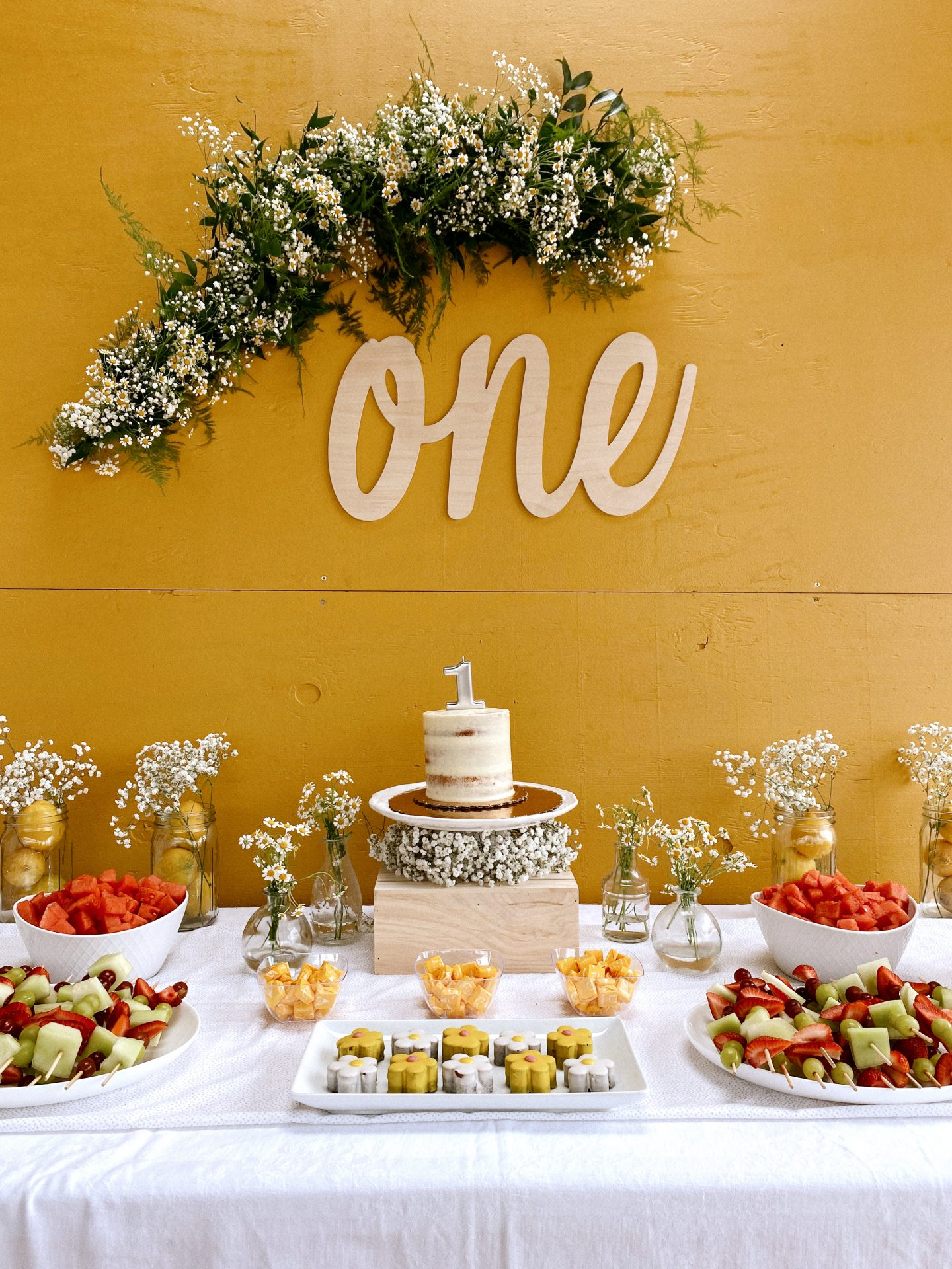 Daisy Theme Party by popular San Diego lifestyle blog, Navy Grace: image of a mustard yellow backdrop, wooden 'one' sign, daisy garland, and a food table with a cake, daisy shaped cakes, fruit skewers, vases filled with baby's breath and daisies, and daisy cupcakes.