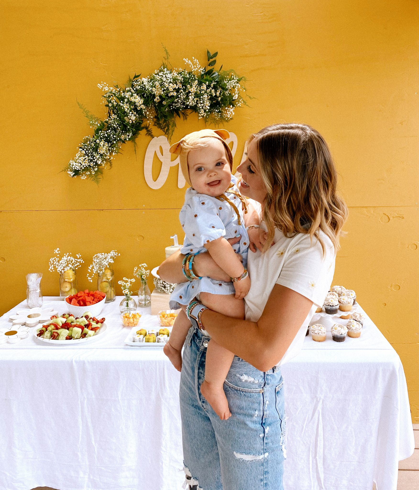 Daisy Theme Party by popular San Diego lifestyle blog, Navy Grace: image of a mustard yellow backdrop, wooden 'one' sign, daisy garland, food table with a cake, daisy shaped cakes, fruit skewers, vases filled with baby's breath and daisies, and daisy cupcakes and a Mom wearing a Sezane Evan t-shirt, Anthropologie Gemma slides, Agolde Jeans, and Anthropologie stack bracelets holding a one year old baby wearing a blue daisy print Zara dress and Briar Baby Honey Bear bonnet.