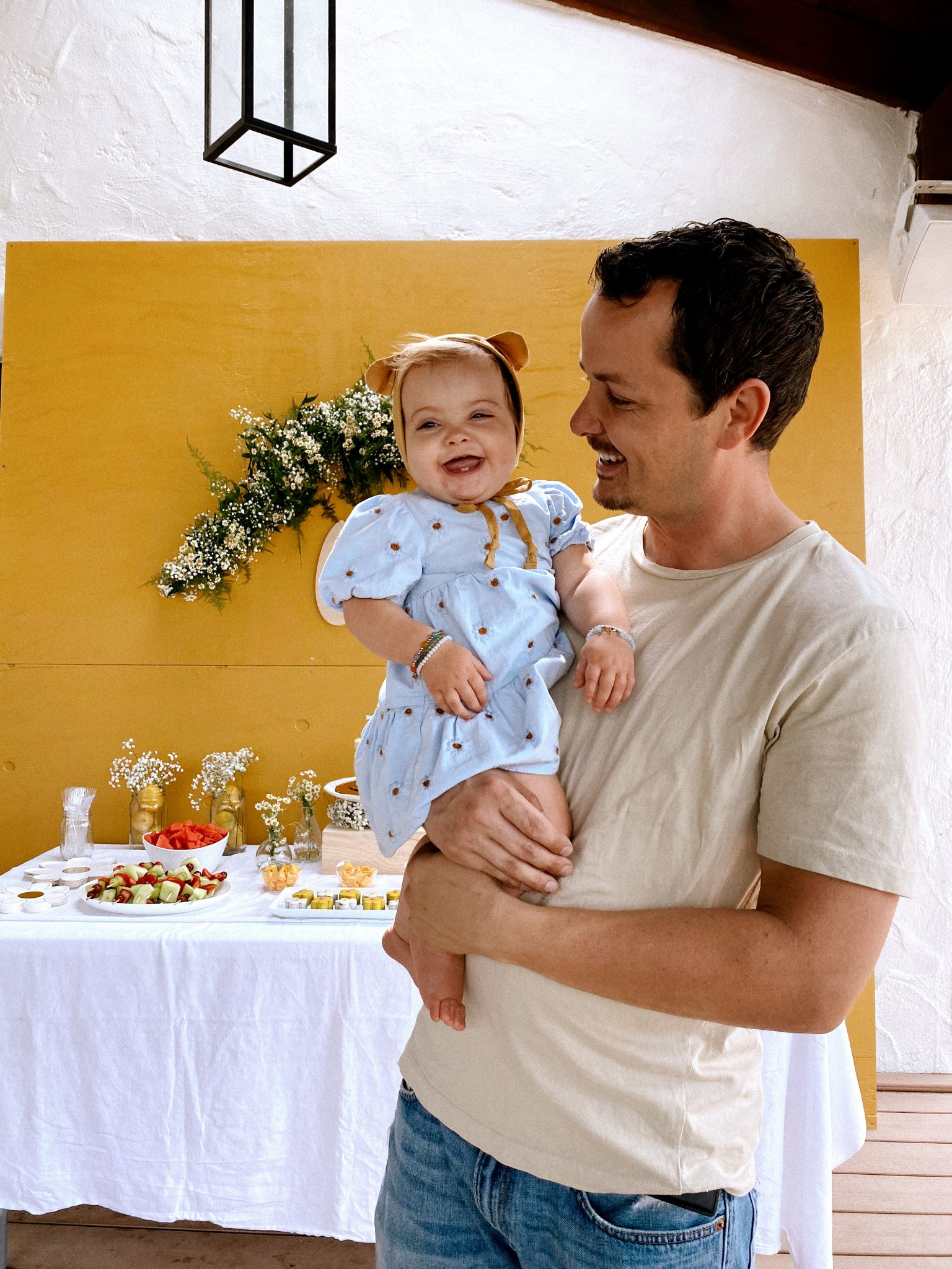 Daisy Theme Party by popular San Diego lifestyle blog, Navy Grace: image of a mustard yellow backdrop, wooden 'one' sign, daisy garland, food table with a cake, daisy shaped cakes, fruit skewers, vases filled with baby's breath and daisies, and daisy cupcakes and a dad holding a one year old baby wearing a blue daisy print Zara dress and Briar Baby Honey Bear bonnet.
