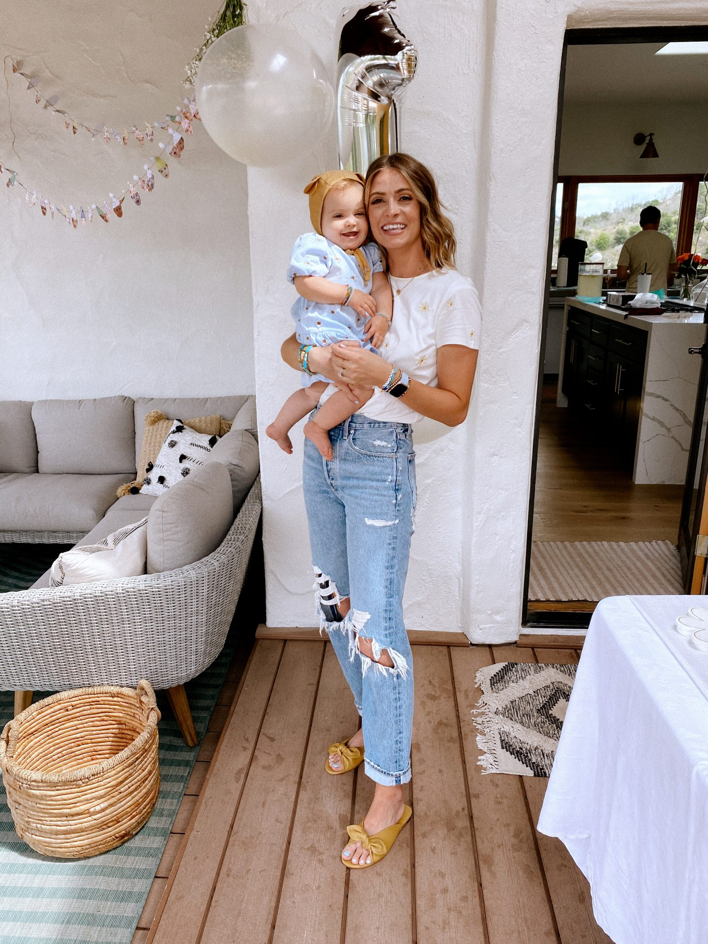 Daisy Theme Party by popular San Diego lifestyle blog, Navy Grace: image of a Mom wearing a Sezane Evan t-shirt, Anthropologie Gemma slides, Agolde Jeans, and Anthropologie stack bracelets holding a one year old baby wearing a blue daisy print Zara dress and Briar Baby Honey Bear bonnet.