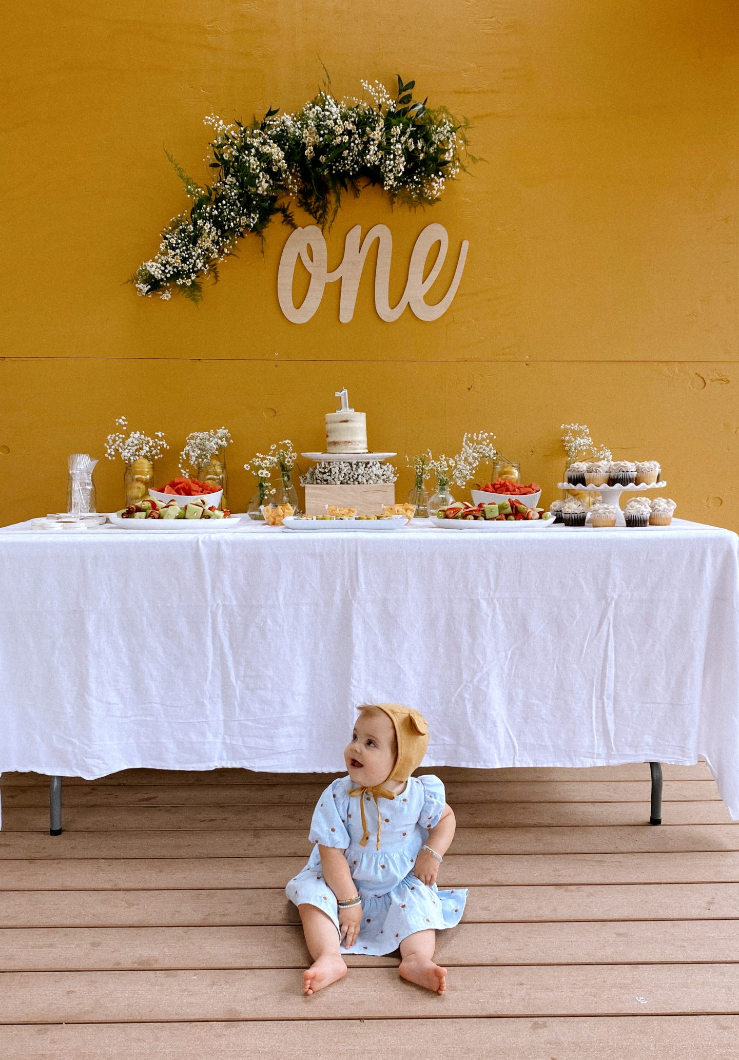 Daisy Theme Party by popular San Diego lifestyle blog, Navy Grace: image of a mustard yellow backdrop, wooden 'one' sign, daisy garland, food table with a cake, daisy shaped cakes, fruit skewers, vases filled with baby's breath and daisies, and daisy cupcakes and a one year old baby sitting in front of the food table wearing a blue daisy print Zara dress and Briar Baby Honey Bear bonnet.