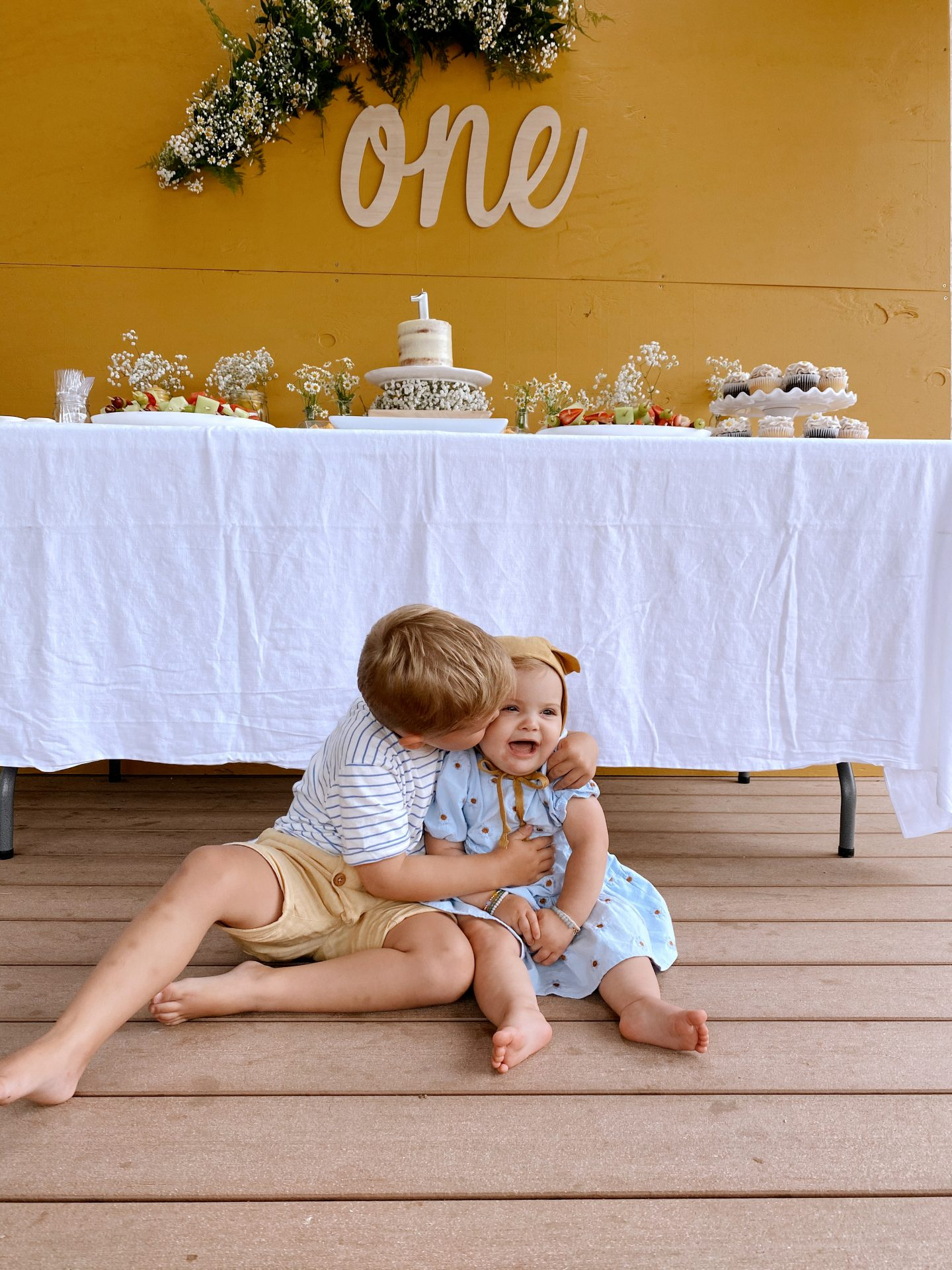 Daisy Theme Party by popular San Diego lifestyle blog, Navy Grace: image of a mustard yellow backdrop, wooden 'one' sign, daisy garland, food table with a cake, daisy shaped cakes, fruit skewers, vases filled with baby's breath and daisies, and daisy cupcakes and a little boy and one year old baby sitting in front of the food table wearing a blue daisy print Zara dress and Briar Baby Honey Bear bonnet.