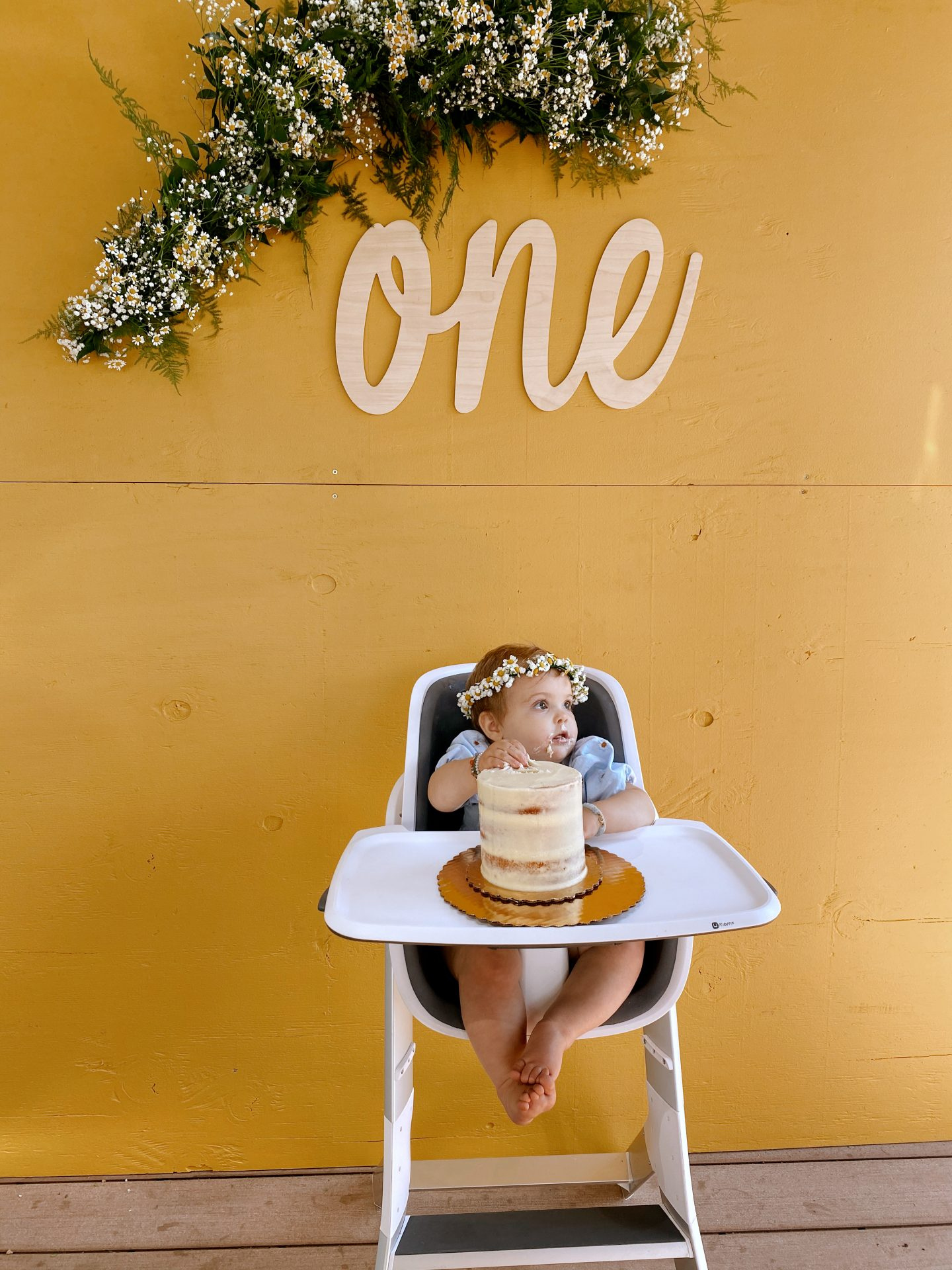 Daisy Theme Party by popular San Diego lifestyle blog, Navy Grace: image of a baby wearing a blue daisy print Zara dress and Briar Baby HONEY BEAR bonnet while sitting in a high chair eating a tiered birthday cake in front of a mustard yellow backdrop with a wooden one sign and a daisy garland.