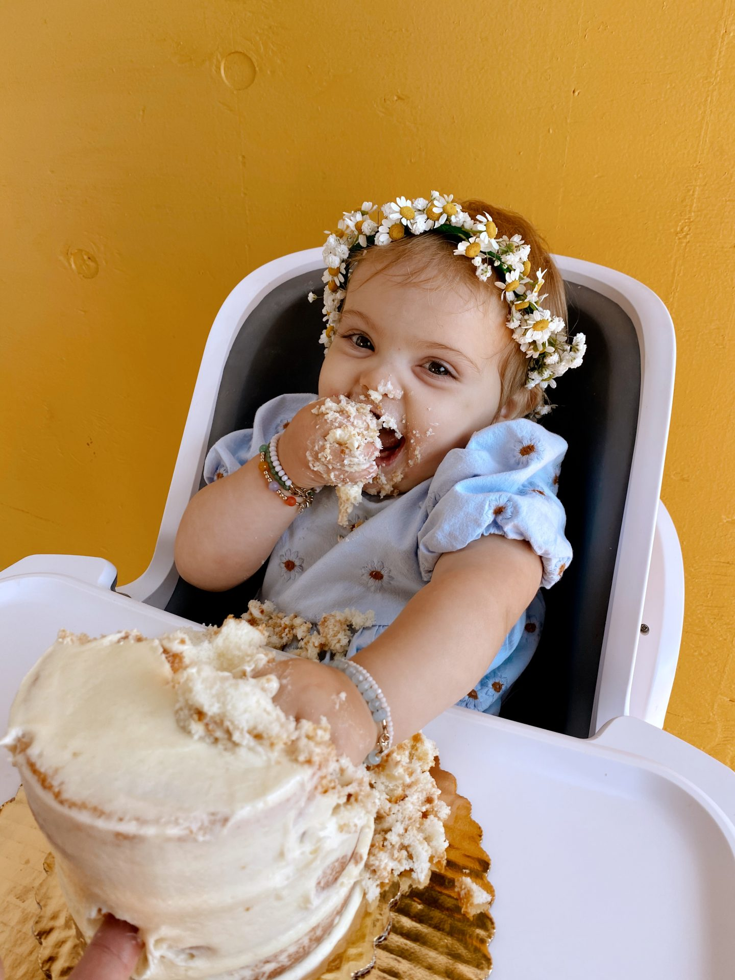 Daisy Theme Party by popular San Diego lifestyle blog, Navy Grace: image of a baby wearing a blue daisy print Zara dress, Briar Baby HONEY BEAR bonnet and daisy crown while sitting in a high chair eating a tiered birthday cake.