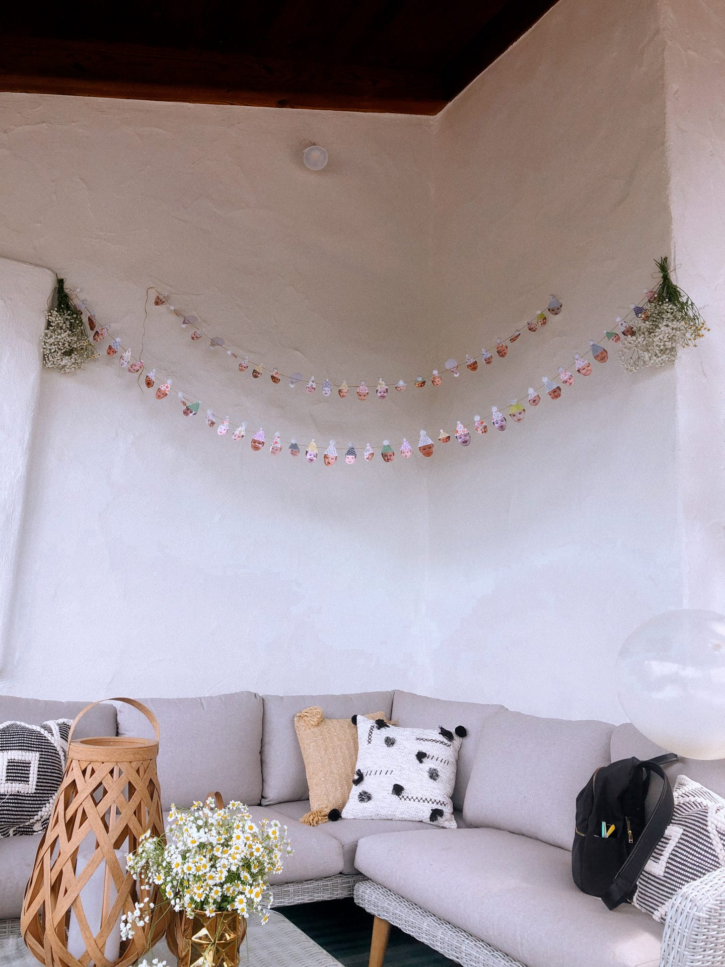 Daisy Theme Party by popular San Diego lifestyle blog, Navy Grace: image of a baby face and party hat craft paper and pom-pom garland hanging above a outdoor grey sectional couch.