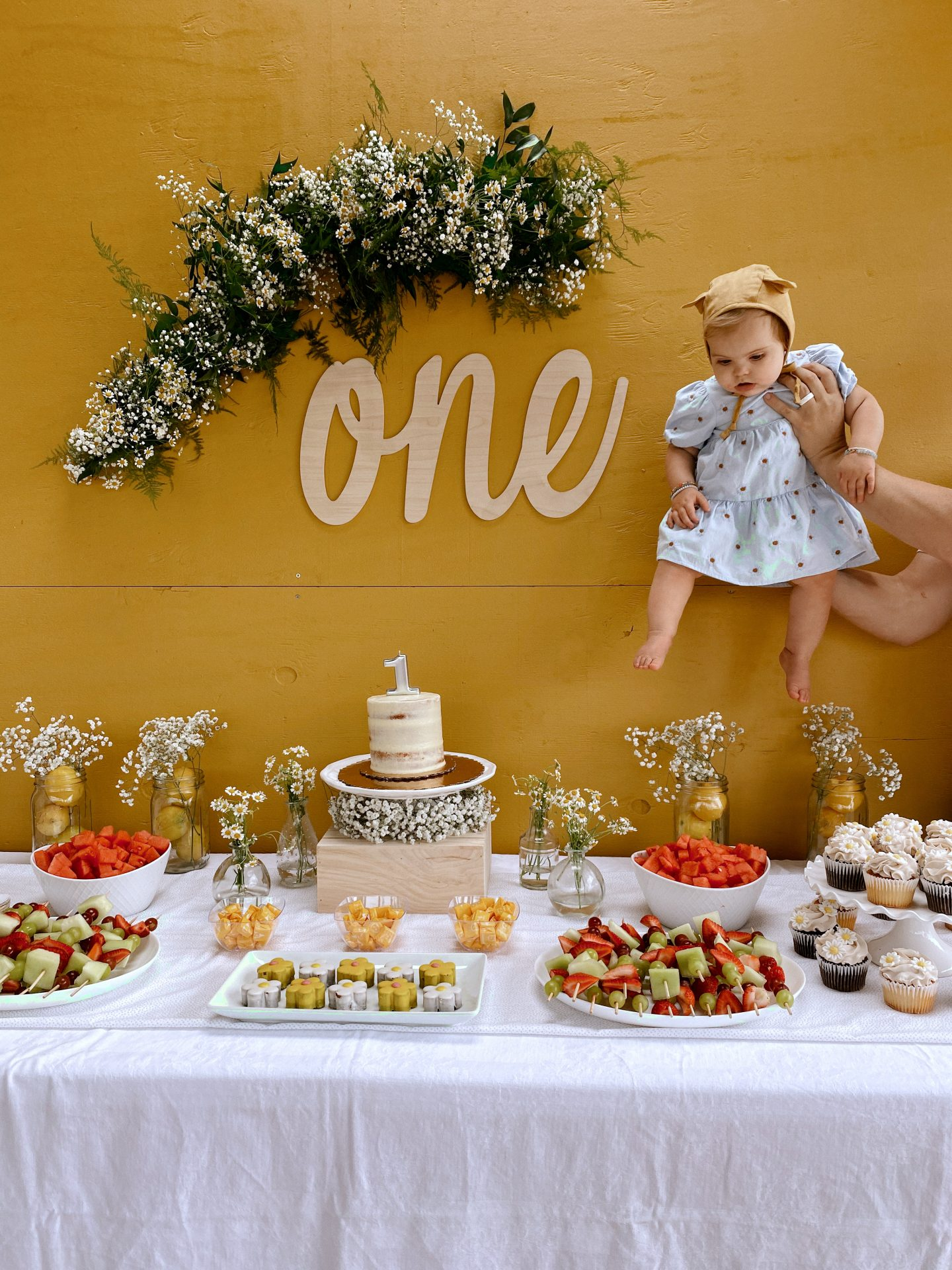 Daisy Theme Party by popular San Diego lifestyle blog, Navy Grace: image of a baby wearing a blue daisy print Zara dress and Briar Baby HONEY BEAR bonnet while being held next to a 'one' sign, daisy garland, and a food table with a cake, daisy shaped cakes, fruit skewers, vases filled with baby's breath and daisies, and daisy cupcakes.