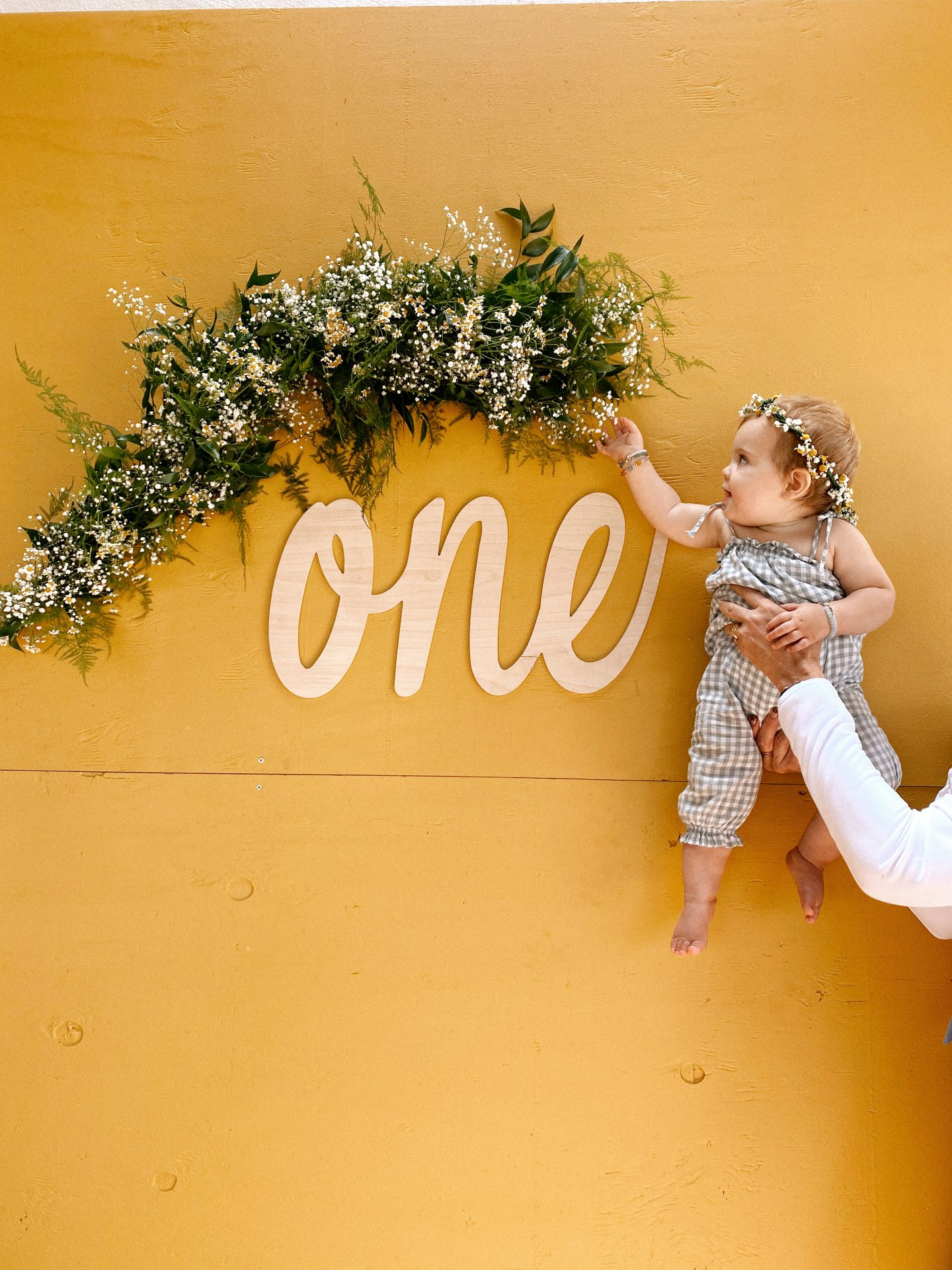 Daisy Theme Party by popular San Diego lifestyle blog, Navy Grace: image of a baby wearing a grey and white gingham romper and a daisy crown while being held next to a wooden 'one' sign, and daisy garland.