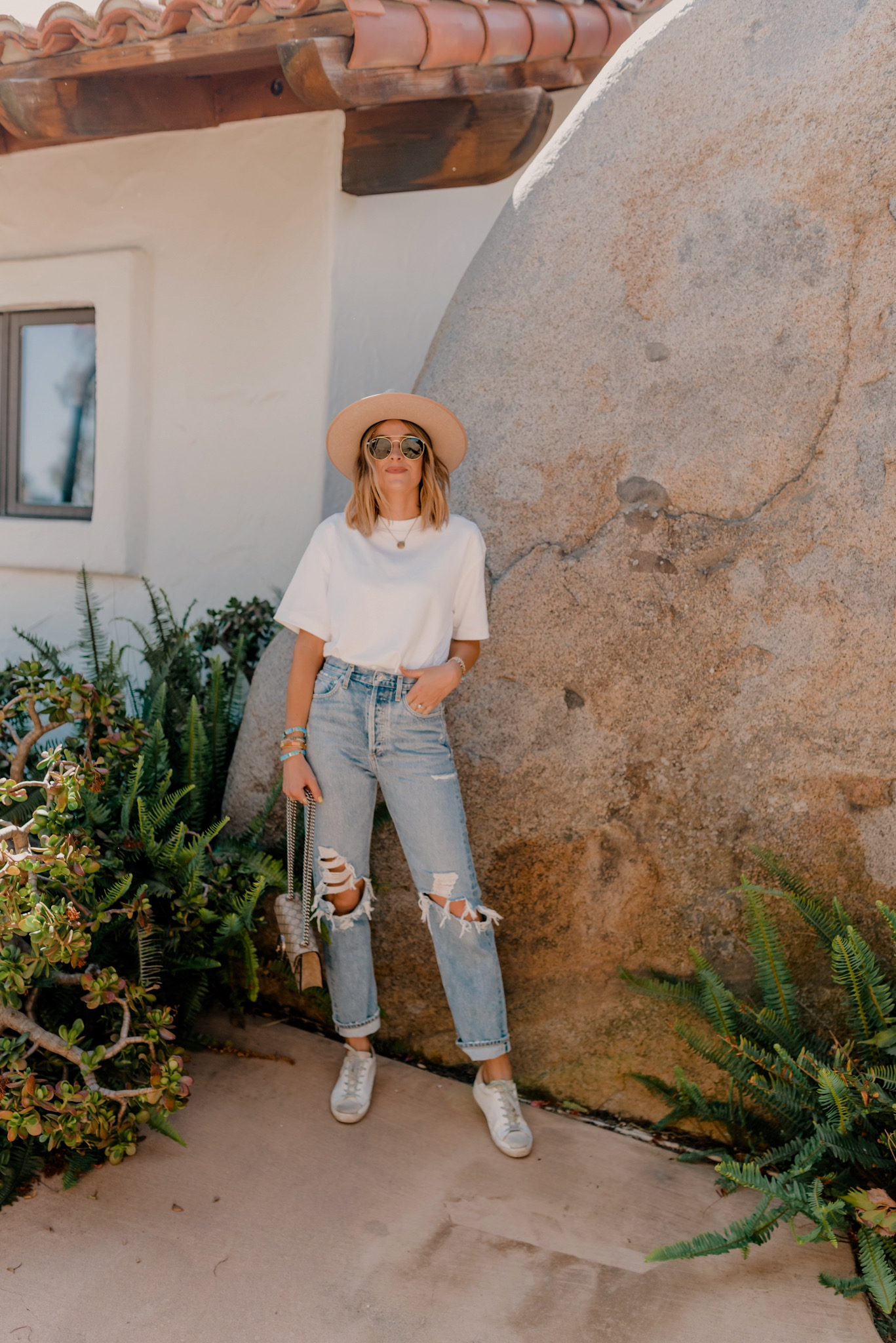 Golden Goose Sneakers by popular San Diego fashion blog, Navy Grace: image of a woman wearing a pair of Golden Goose distressed Superstar sneakers, 90s Mid Rise Loose Fit  AGOLDE brand jeans, Target Women's Short Sleeve T-Shirt, Gigi Pip Monroe Oatmeal rancher hat, and Ray-Ban sunglasses.