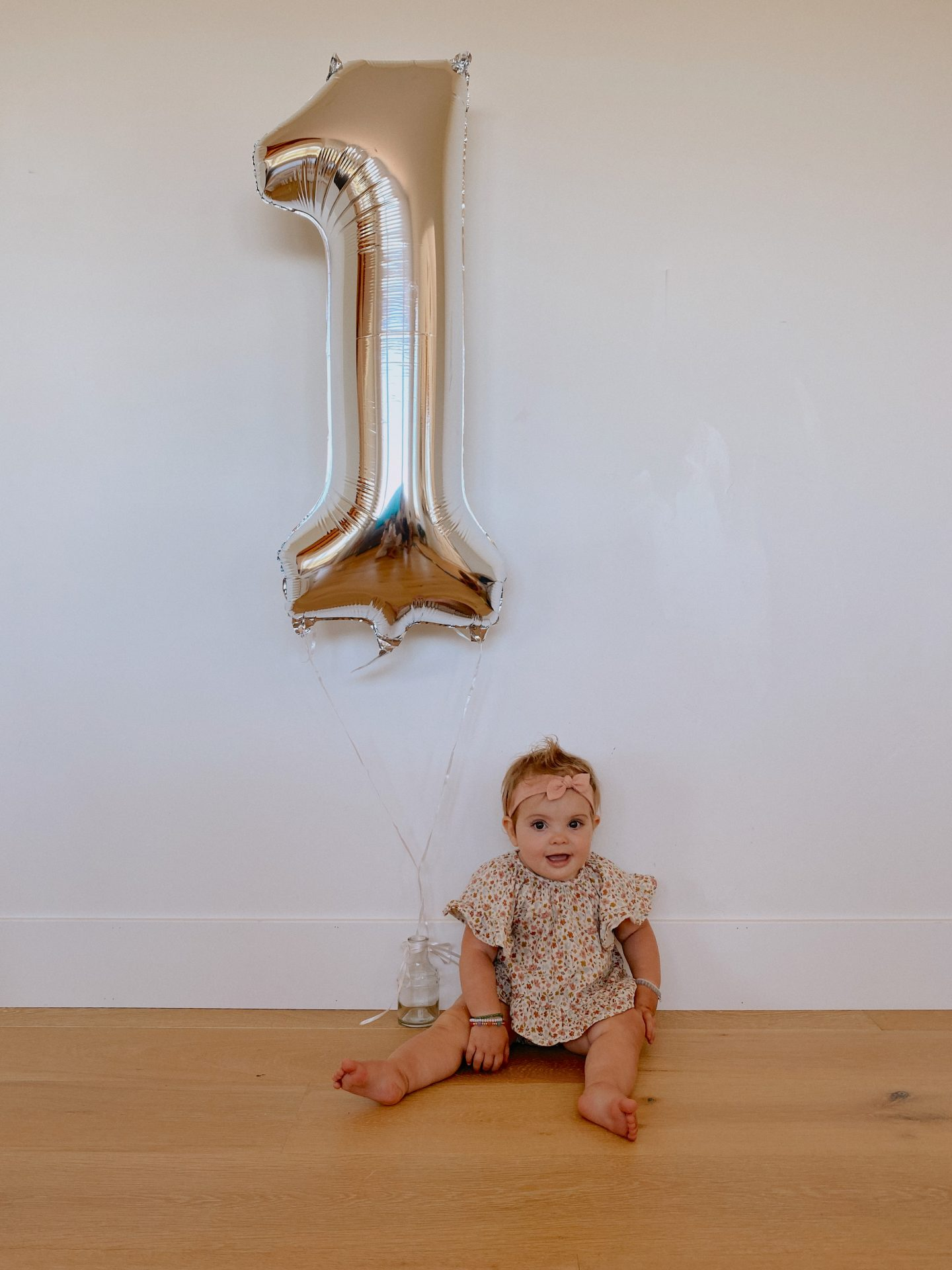 Daisy Theme Party by popular San Diego lifestyle blog, Navy Grace: image of a baby sitting next to a silver helium filled number 1 balloon.