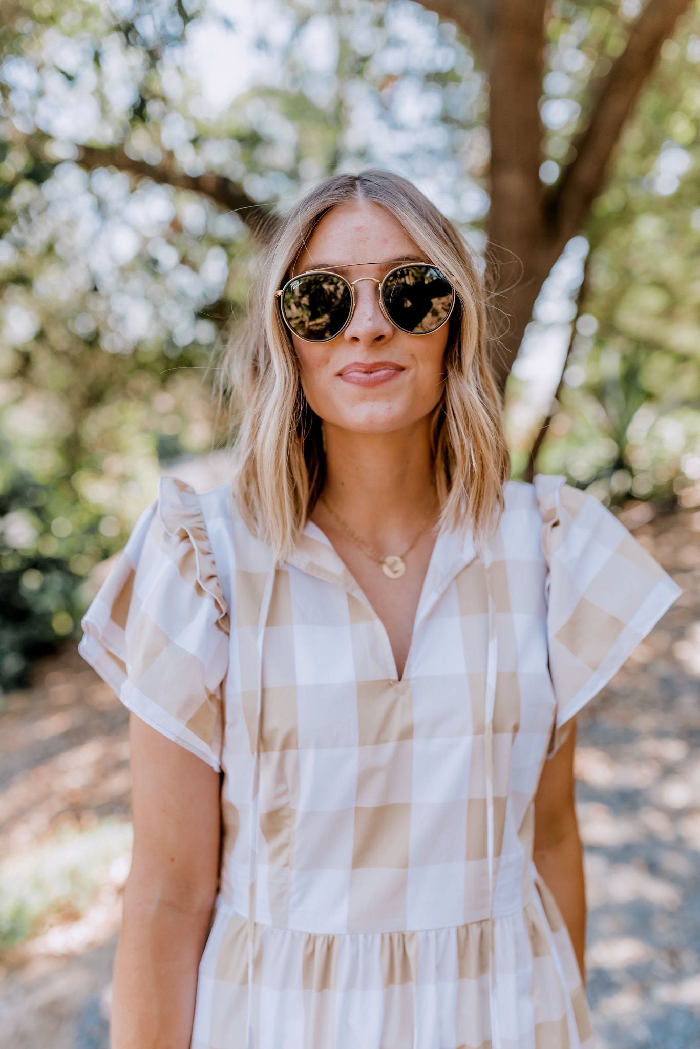 New Arrivals by popular San Diego fashion blog, Navy Grace: image of a woman standing outside on a gravel path and wearing a Target Women's Bell Short Sleeve Dress, Anthropologie Gemma Bow Slide Sandals, Ray-Ban sunglasses, and holding a Nordstrom Gucci Small Matelassé Leather Shoulder Bag.