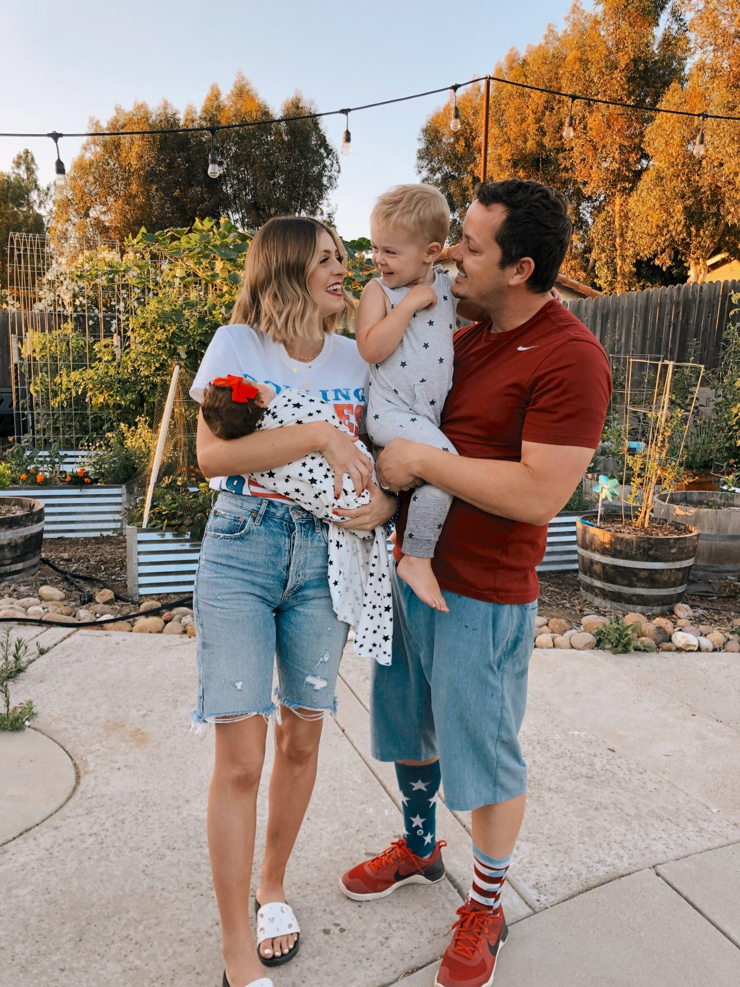 4th of July Fashion by popular San Diego fashion blog, Navy Grace: image of a mom and dad standing together while holding their kids and wearing AGolde jean shorts, Rolling Stones t-shirt, grey star print jumper, red nike sneakers, white slide sandals, and red nike t-shirt.
