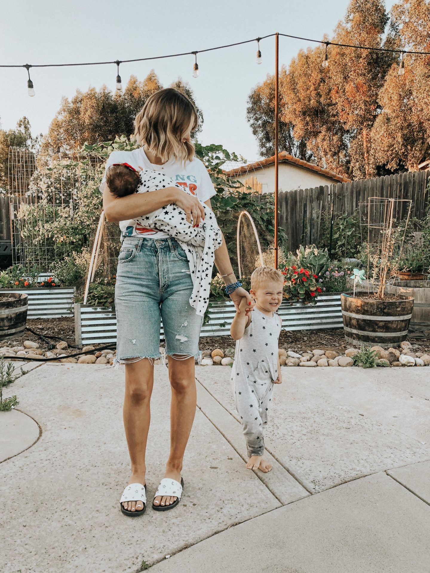 4th of July Fashion by popular San Diego fashion blog, Navy Grace: image of a mom and dad standing together while holding their kids and wearing AGolde jean shorts, Rolling Stones t-shirt, grey star print jumper.