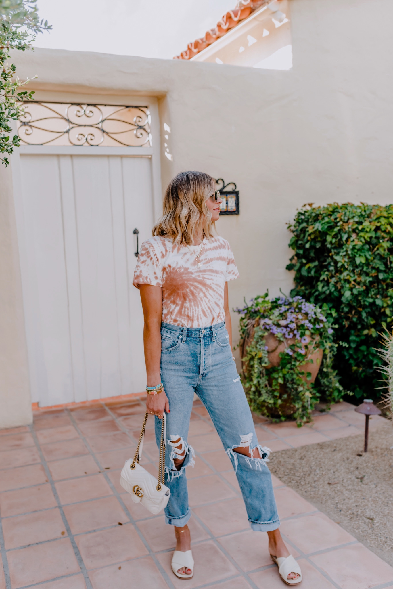 Tie Dye Fashion by popular San Diego fashion blog, Navy Grace: image of a woman wearing a Evereve The Tie-Dye Box-Cut Tee, AGolde jeans, Evereve The Day Crossover Sandal, and holding a Nordstrom GUCCI Small Matelassé Leather Shoulder Bag.