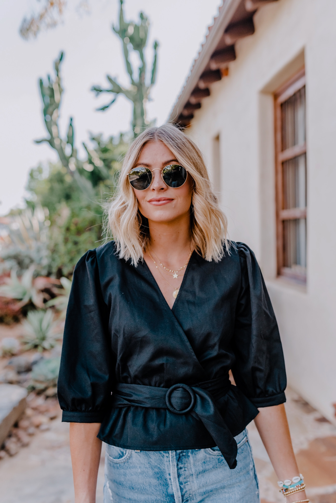 Date Night Outfits by popular San Diego fashion blog, Navy Grace: image of a woman wearing a BB Dakota DYNASTY PUFF SLEEVE TOP, Steve Madden LOFT BLACK SNAKE heel sandal, Revolve Agolde 90s Mid Rise Loose Fit jeans, Gorjana Astrology Coin Necklace, and Ray Ban ROUND DOUBLE BRIDGE @COLLECTION sunglasses.