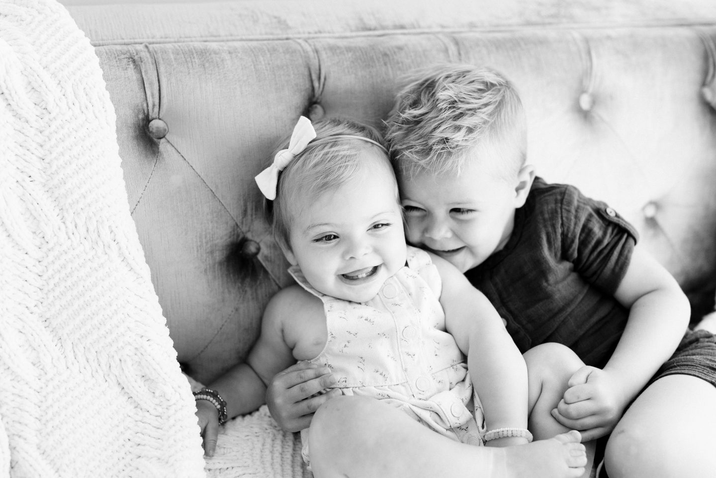 One Year Old Milestones by popular San Diego motherhood blog, Navy Grace: image of a baby girl and her brother sitting together on a grey tuft couch.