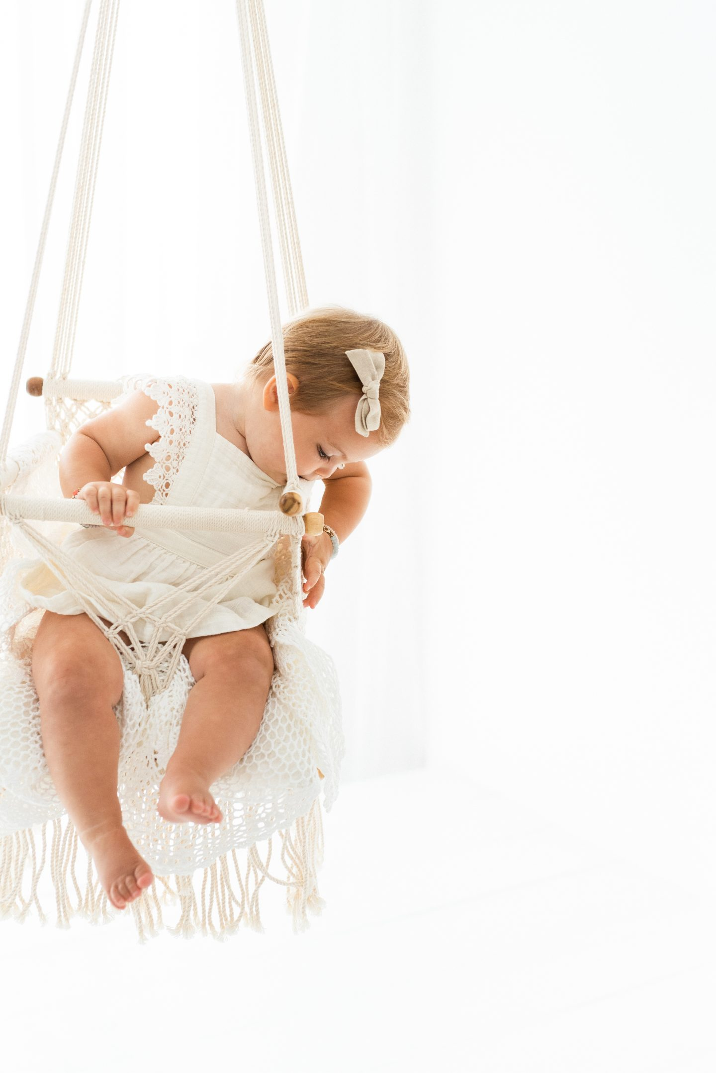One Year Old Milestones by popular San Diego motherhood blog, Navy Grace: image of a baby girl wearing a white dress and sitting in a macrame swing.