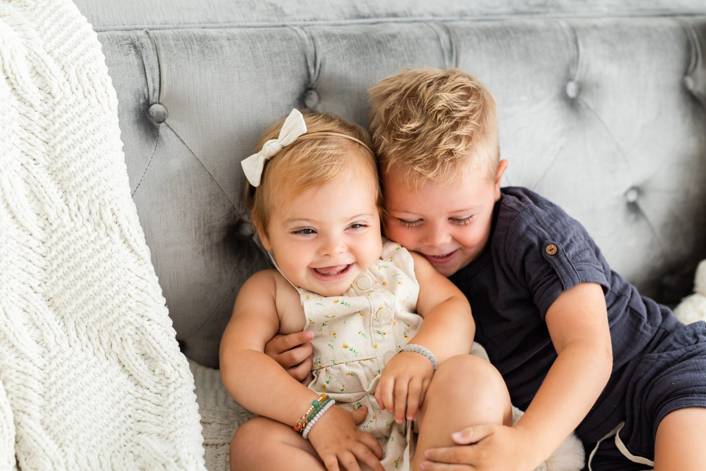 One Year Old Milestones by popular San Diego motherhood blog, Navy Grace: image of a baby girl and her young brother snuggling on a grey tuft couch.