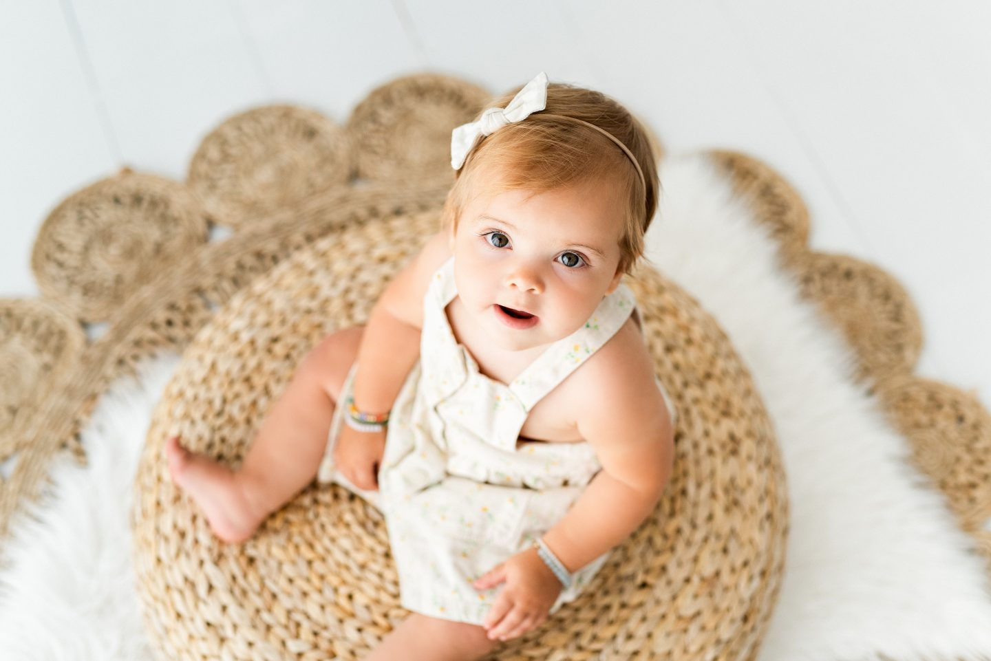 One Year Old Milestones by popular San Diego motherhood blog, Navy Grace: image of a baby girl wearing a flower print dress and sitting on a straw ottoman.