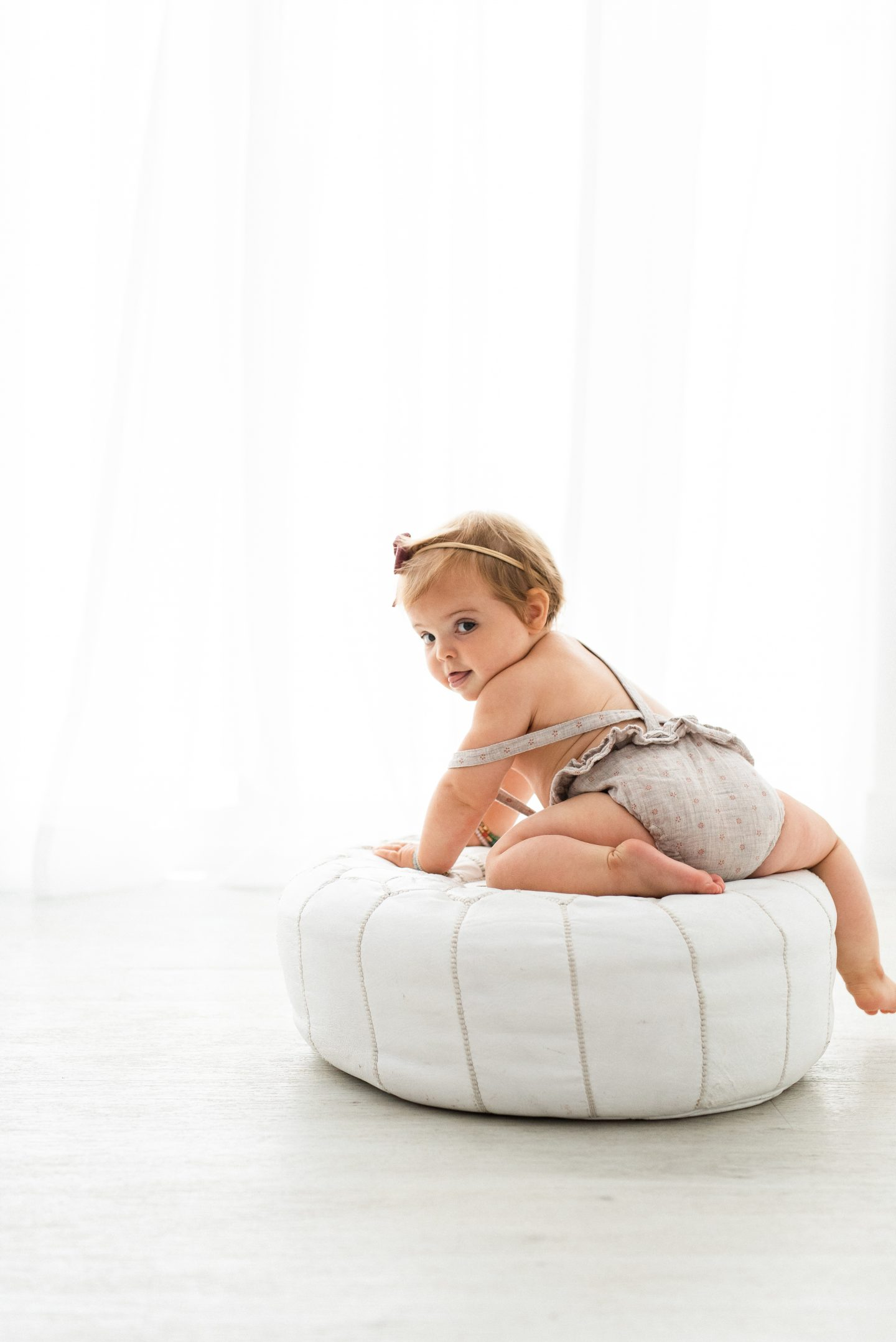 One Year Old Milestones by popular San Diego motherhood blog, Navy Grace: image of a baby girl wearing a romper and sitting on a white leather ottoman.