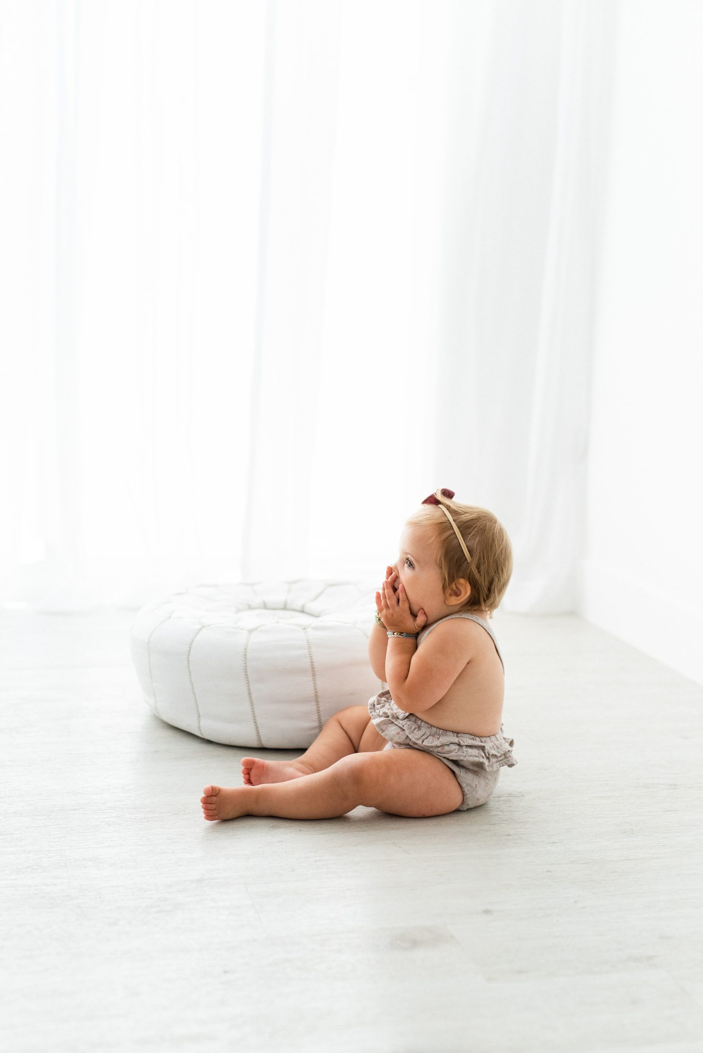 One Year Old Milestones by popular San Diego motherhood blog, Navy Grace: image of a baby girl wearing a romper and sitting on a white wood floor.