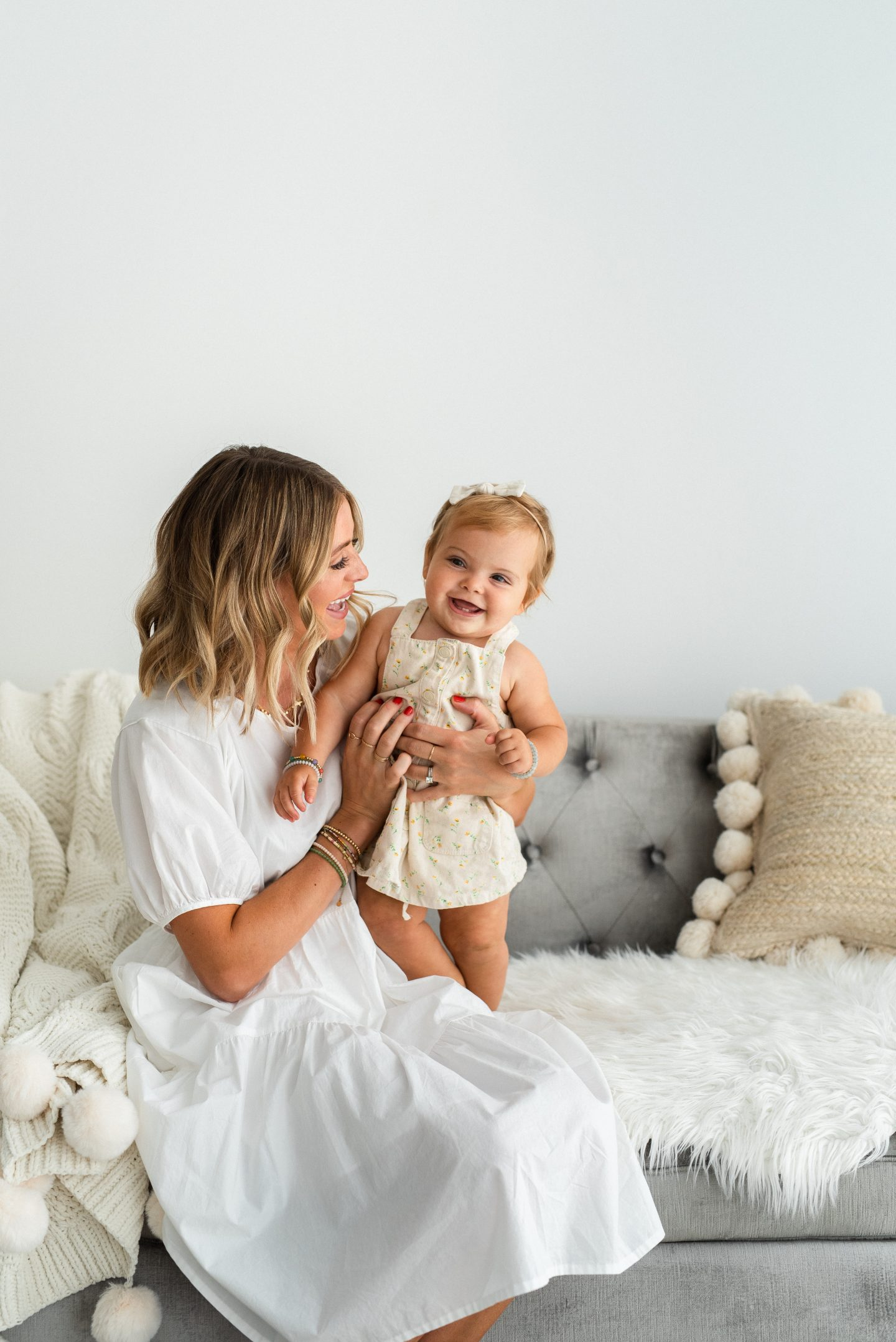 One Year Old Milestones by popular San Diego motherhood blog, Navy Grace: image of a mom sitting on a grey tuft couch and holding her baby girl on her lap.